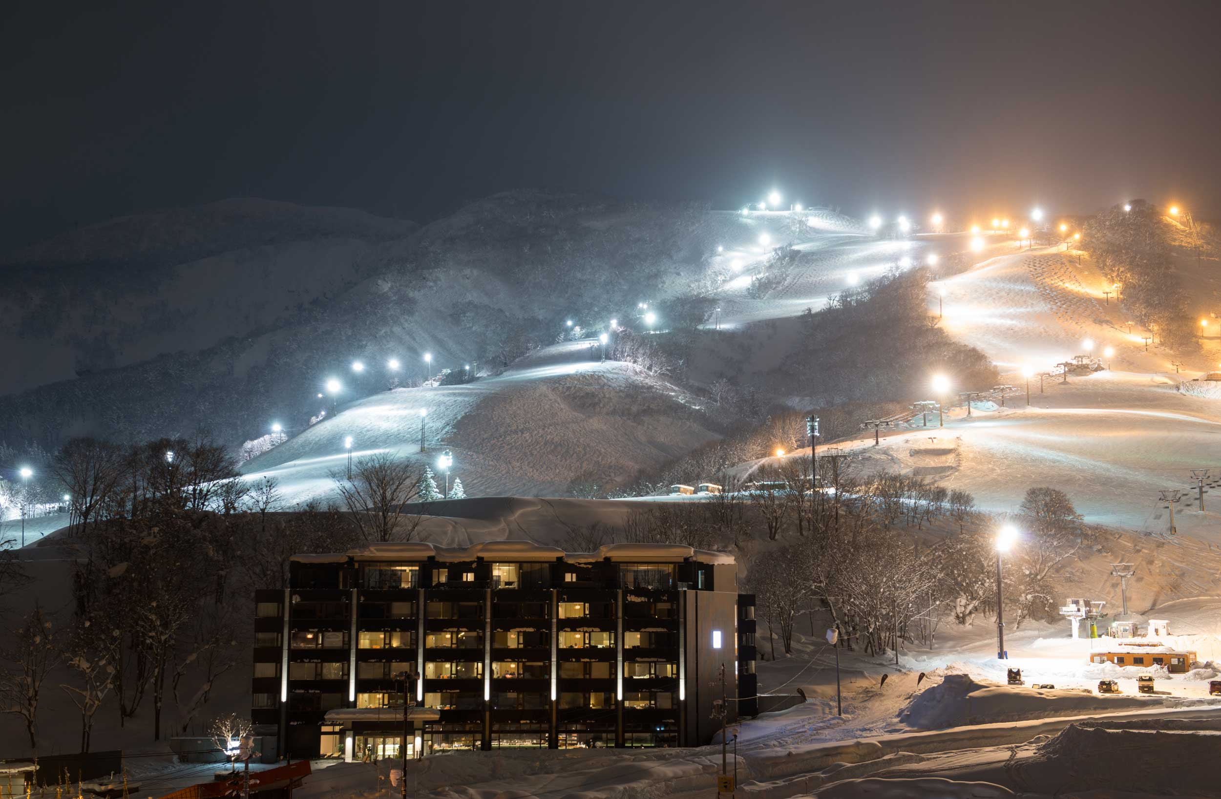 Night view of a building with lighted up ski slopes behind it in Niseko, Japan