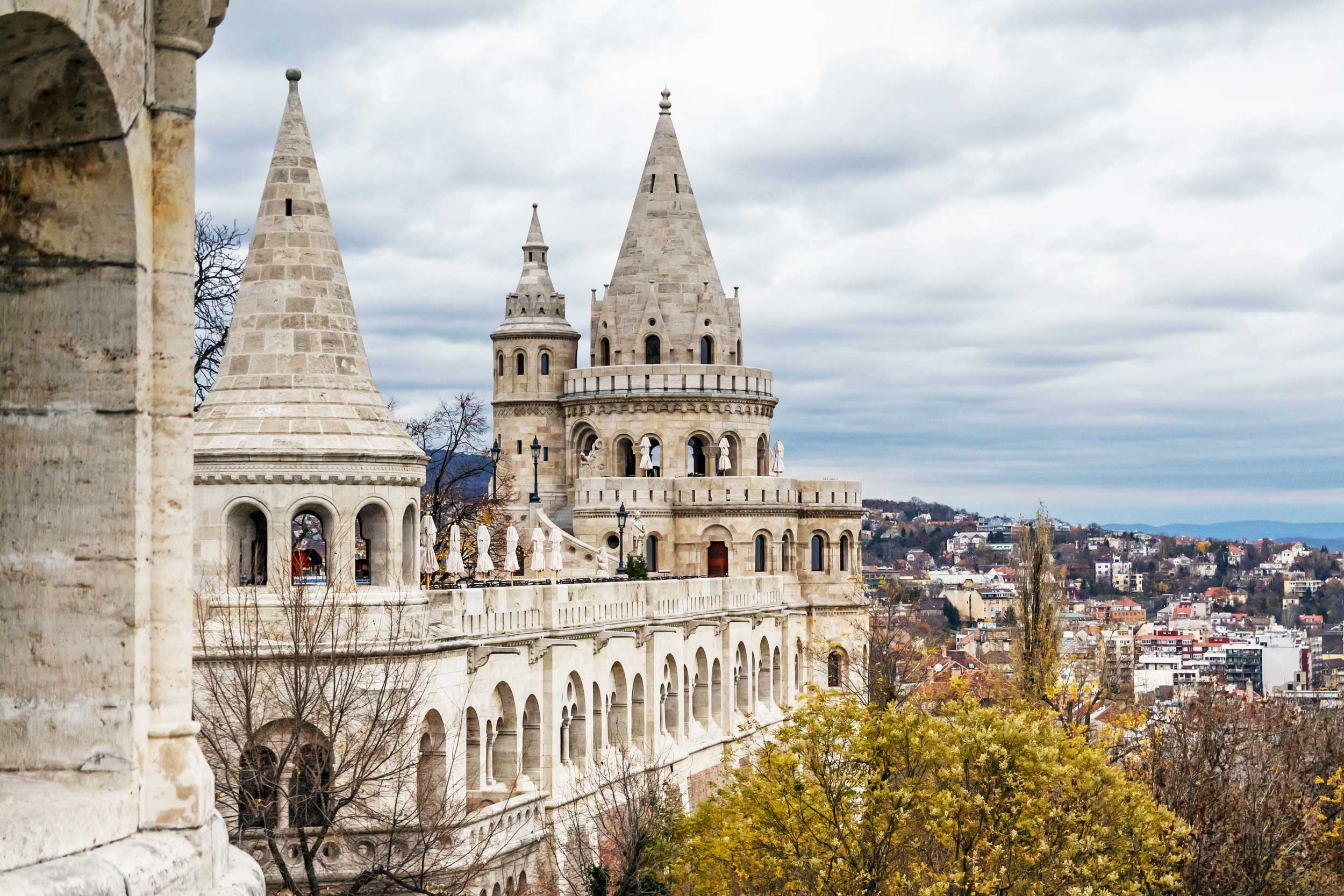 A medieval stone building with three turrets overlooking Budapest, Hungary