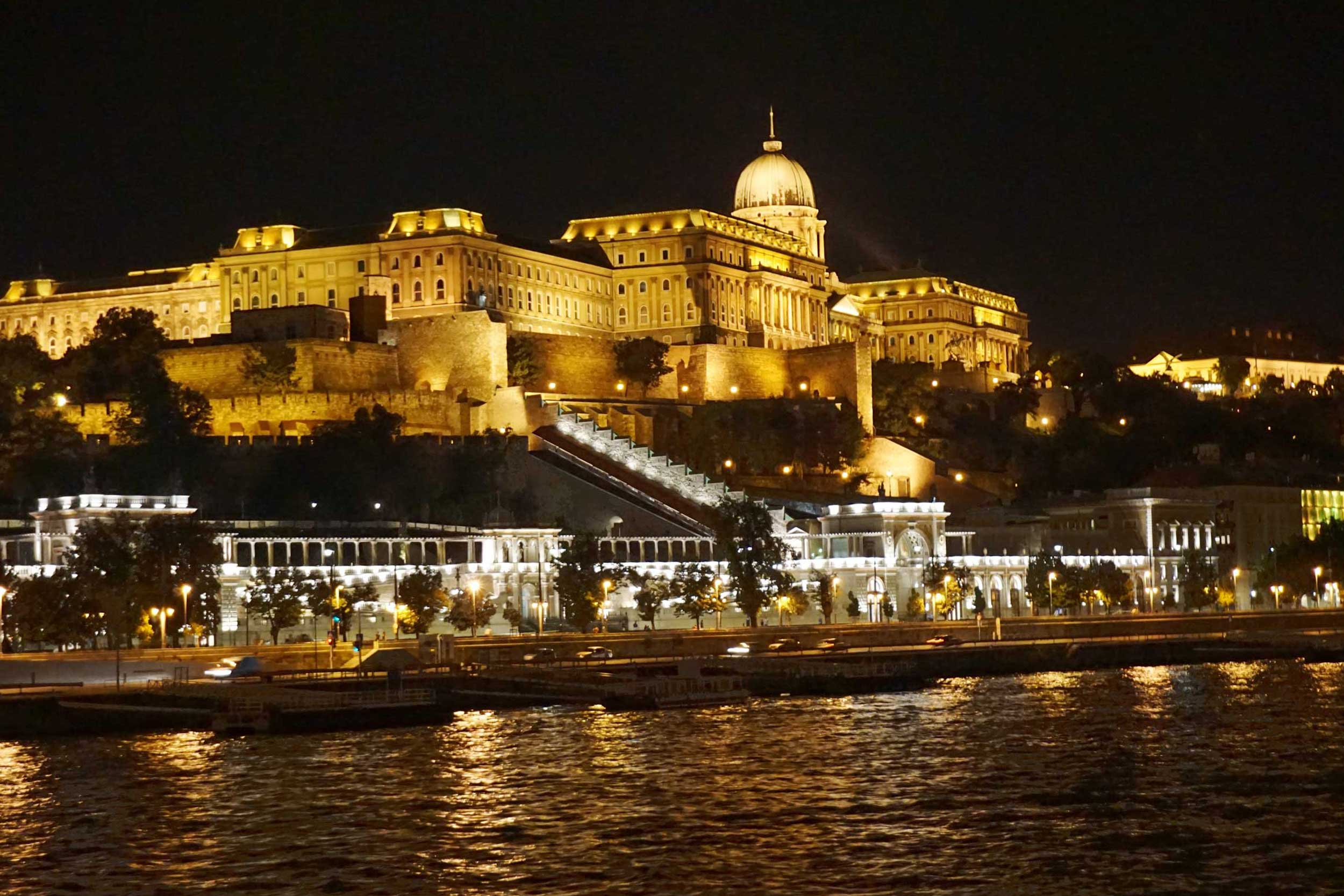 Large castle at night bathed in yellow light with steps leading down to lighted buildings by a river bank, Budapest