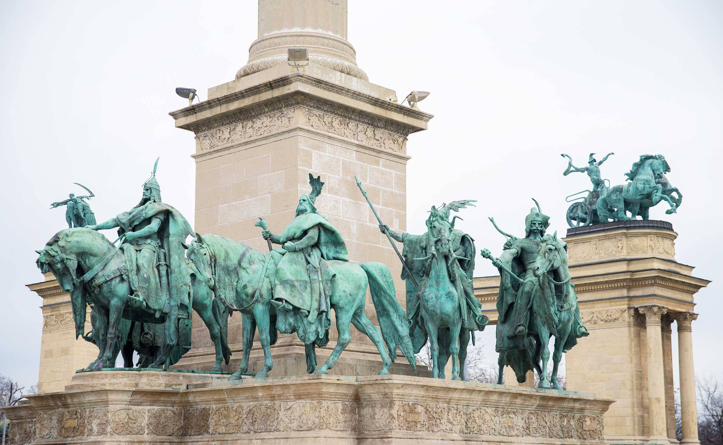Green patinaed horsemen carrying spears around the base of an obelisk, Budapest