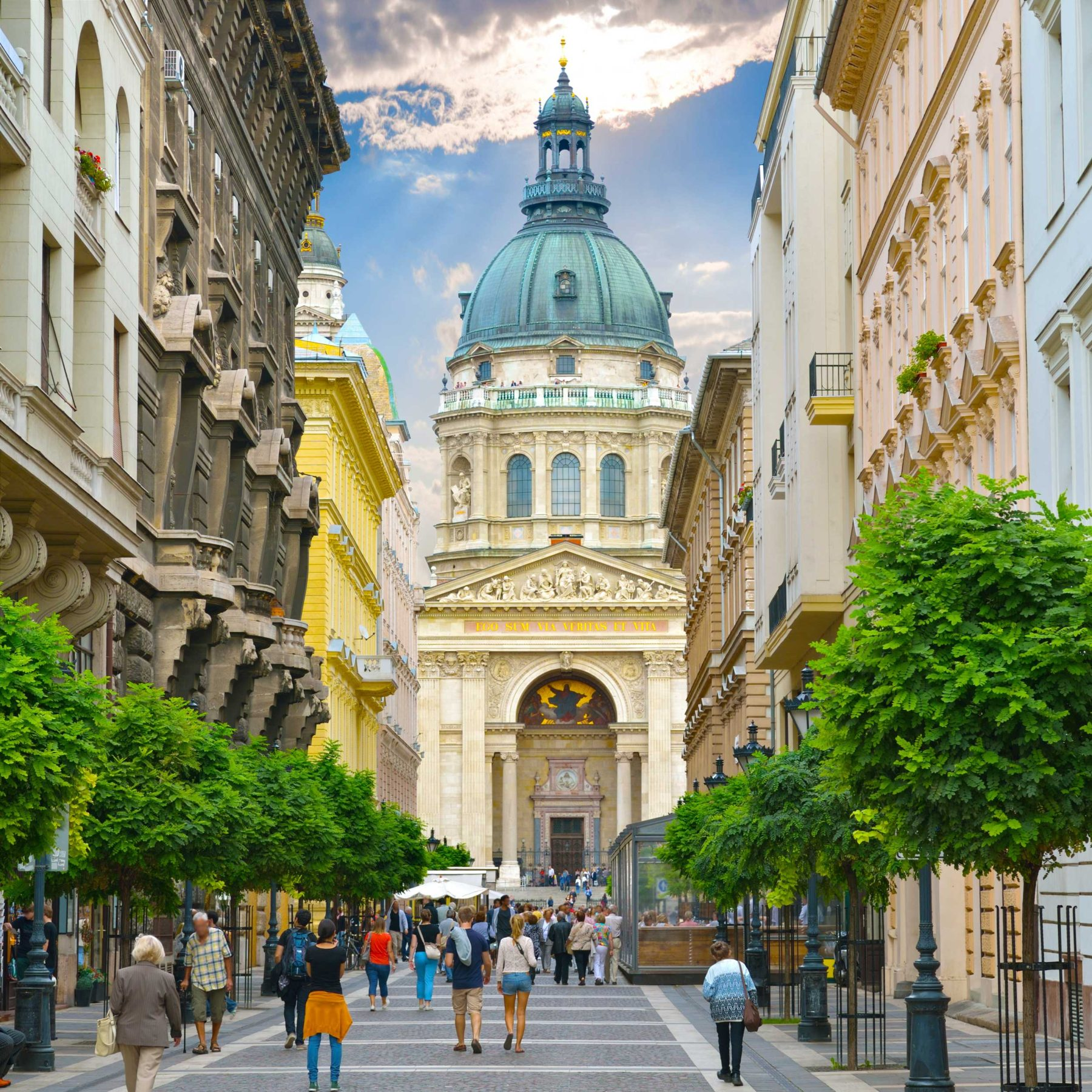Street with people walking through it and leading up to a tall, looming basilica with a blue dome, Budapest
