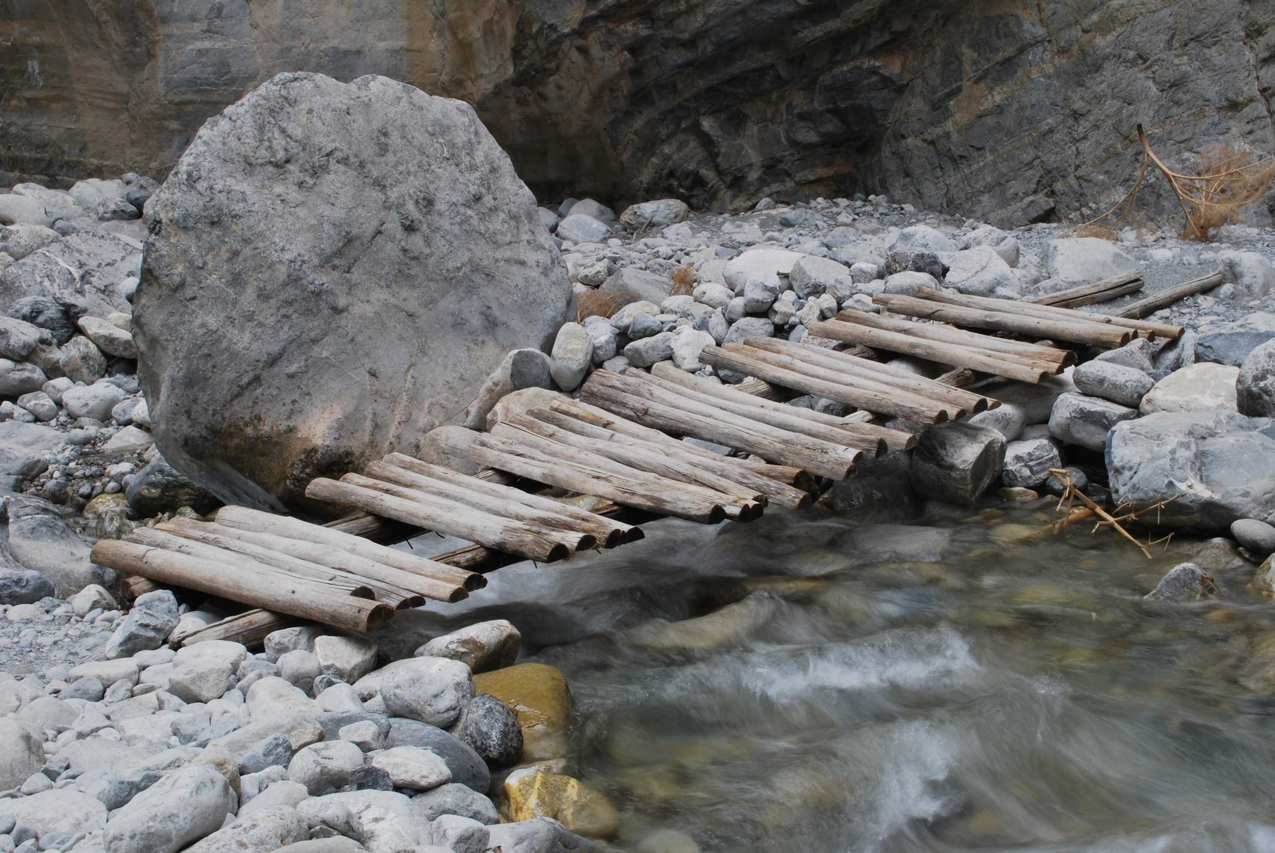 A makeshift wooden bridge fording a stream by a huge boulder in the Samaria Gorge, Crete