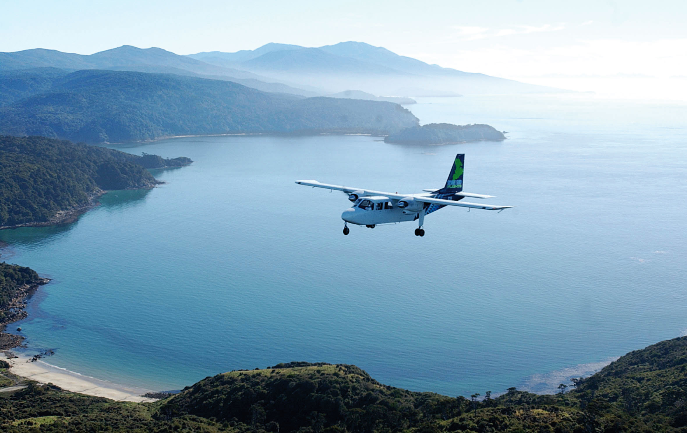 Small 6-seater aeroplane flying over a stretch of water with lush forested hills either side