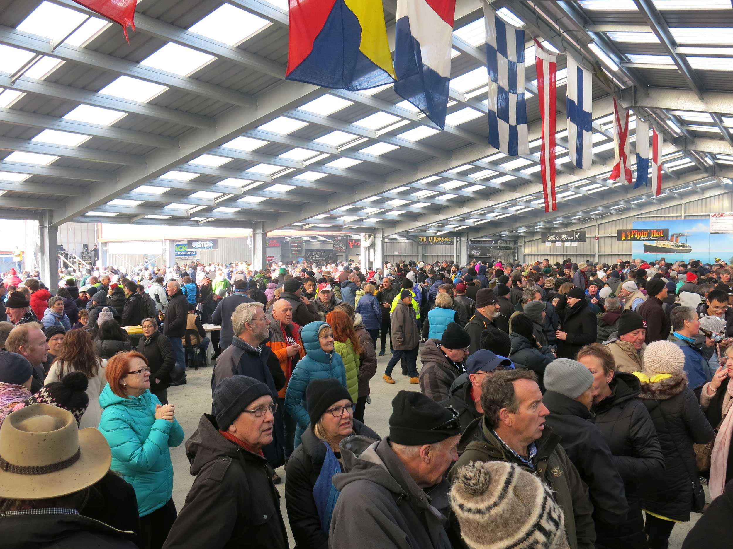 Crowd of people dressed in warm clothing in a metal shed, Bluff, New Zealand