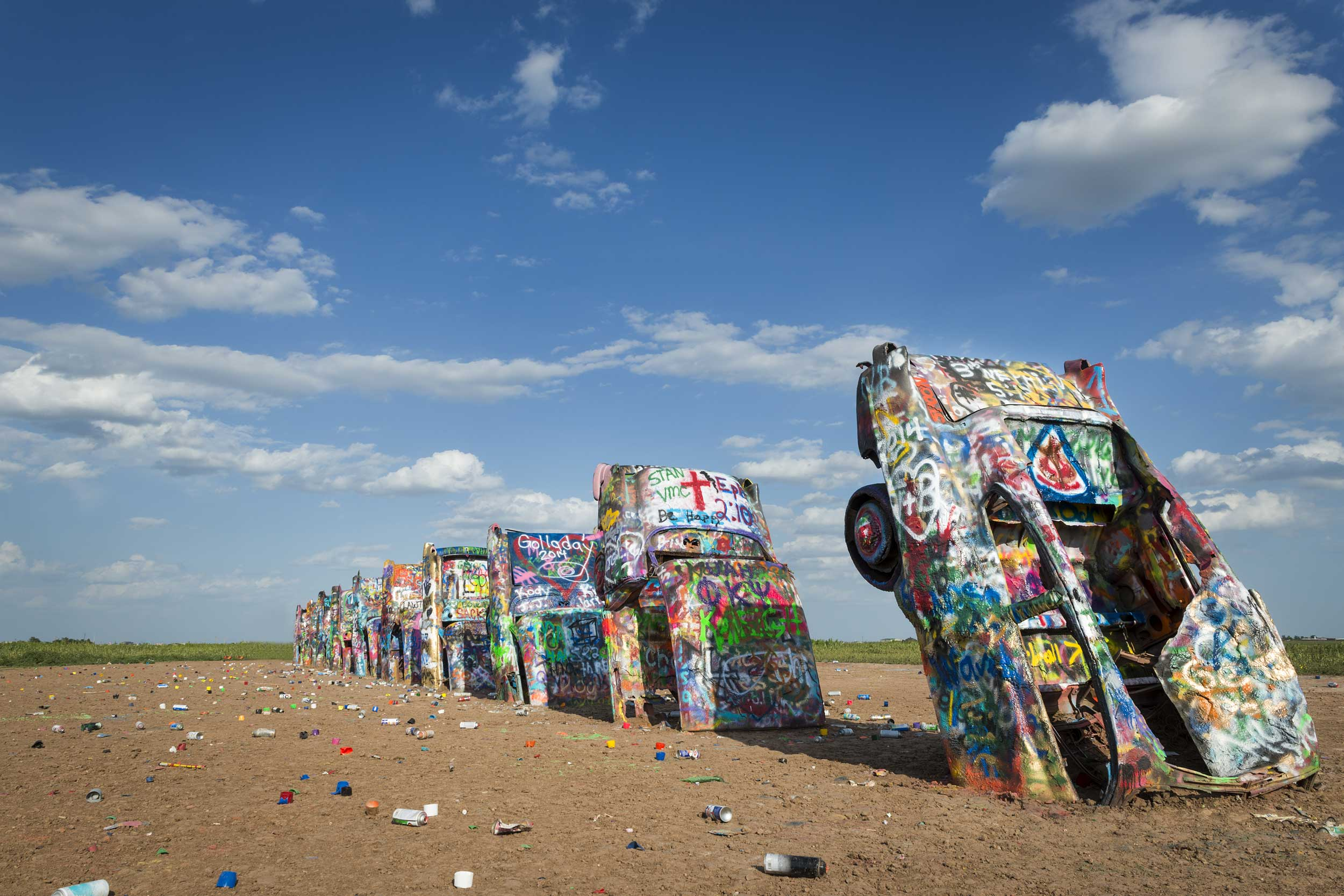 Row of brightly painted Cadillacs buried nose down in the sand, Texas, USA