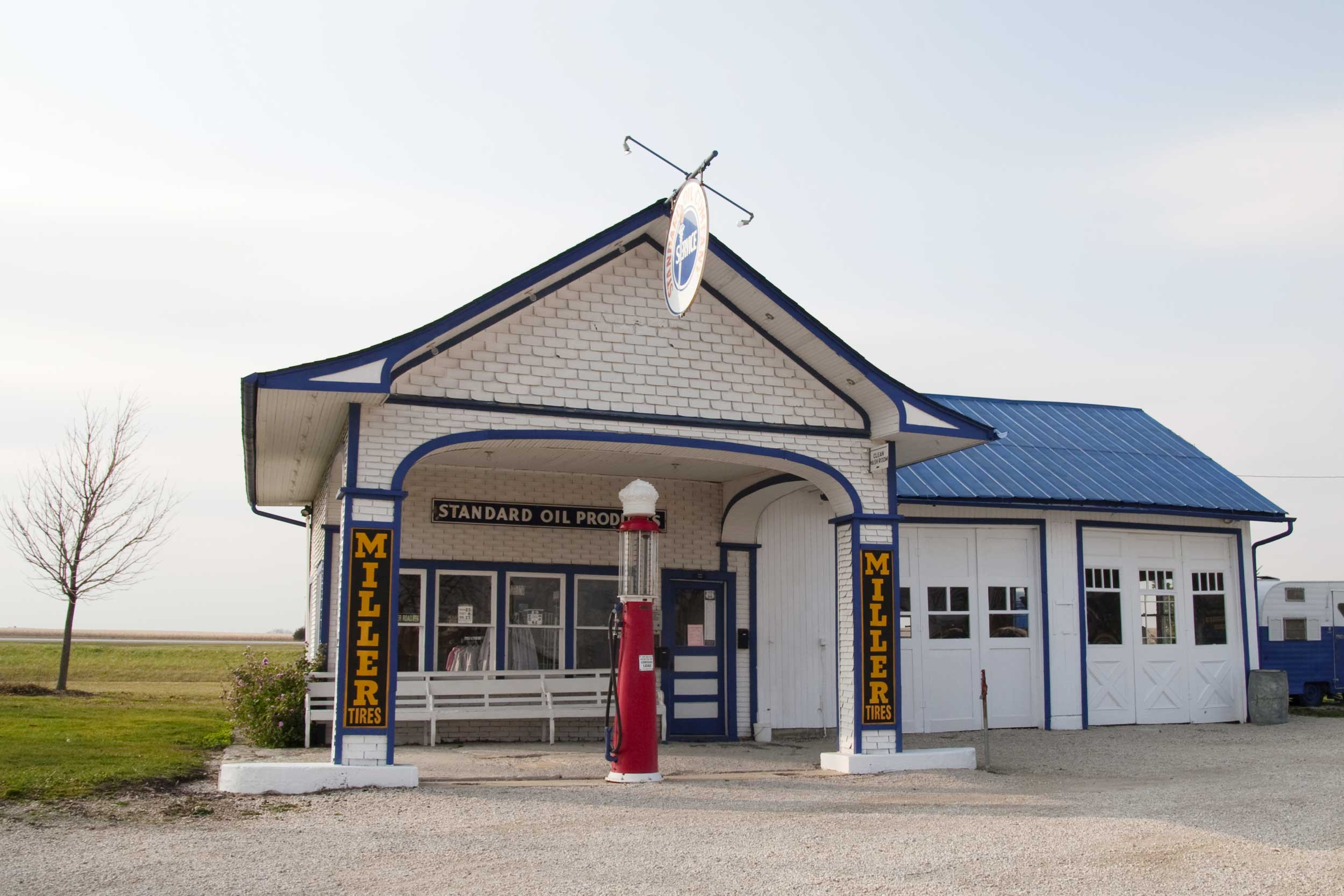 Gas station with blue roof, white walls and a red glass-topped petrol pump in Illinois, USA