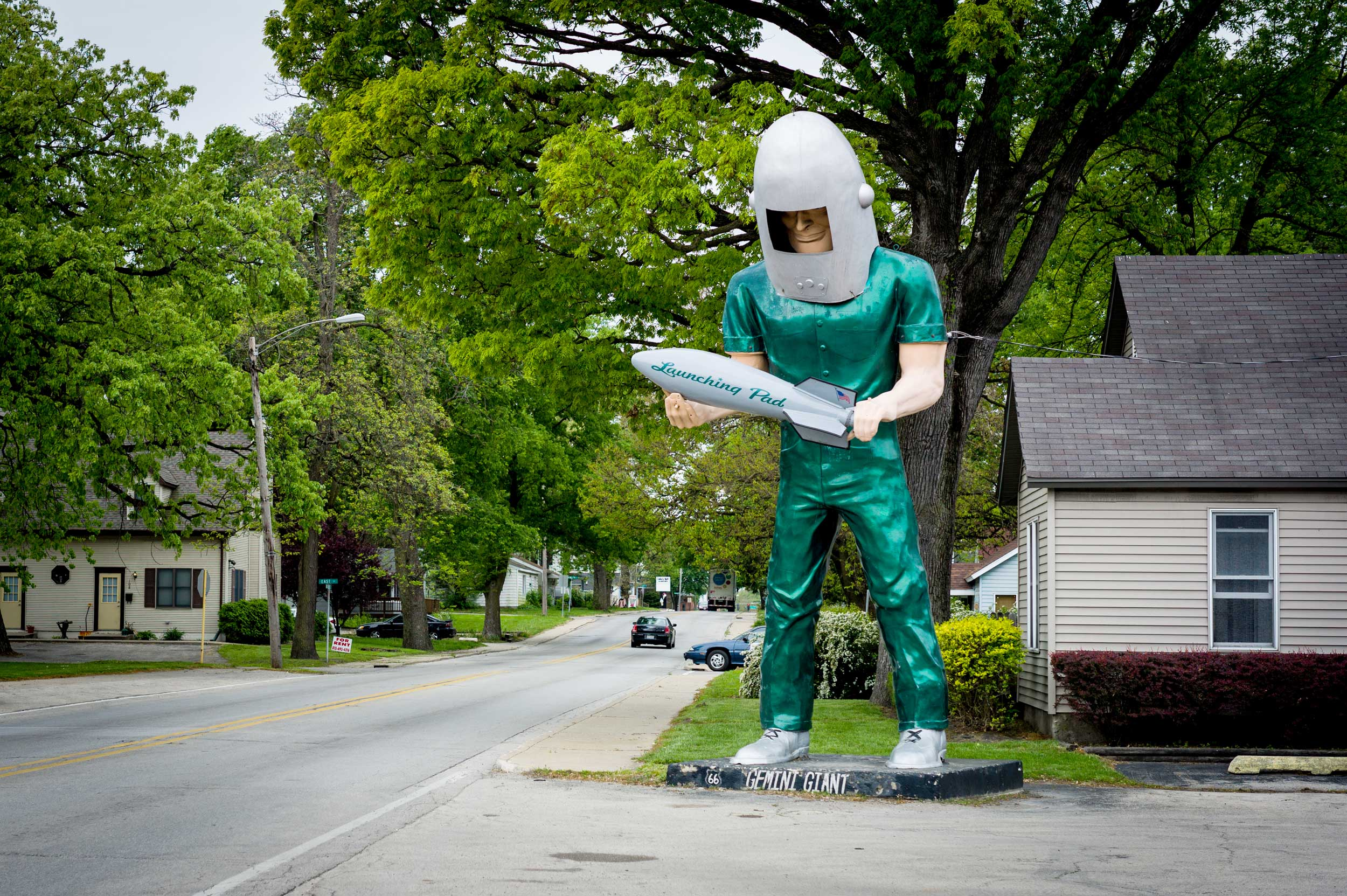 Giant statue of a man in a green spacesuit and helmet holding a rocket on a street corner with some cars in Illinois