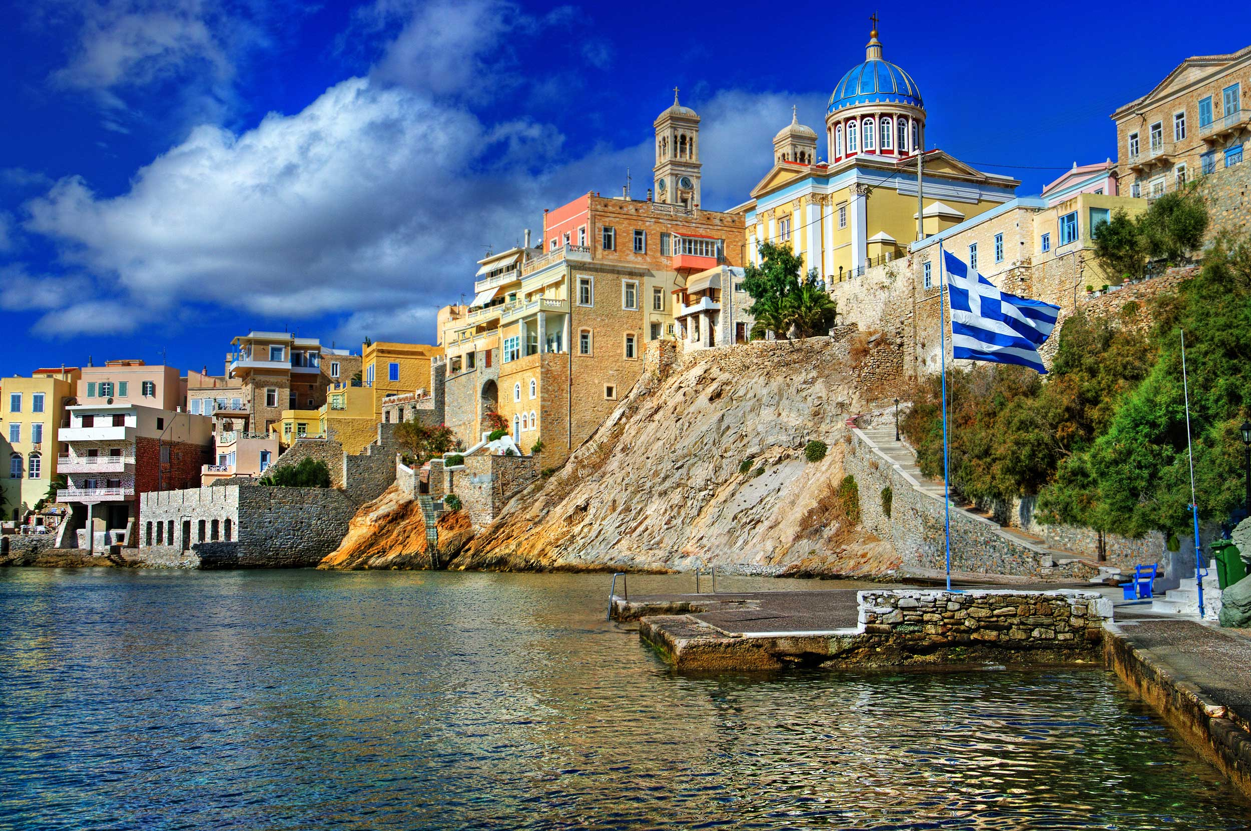 Jetty below a town set on rocks above it with a deep blue-domed building against the skyline in Greece