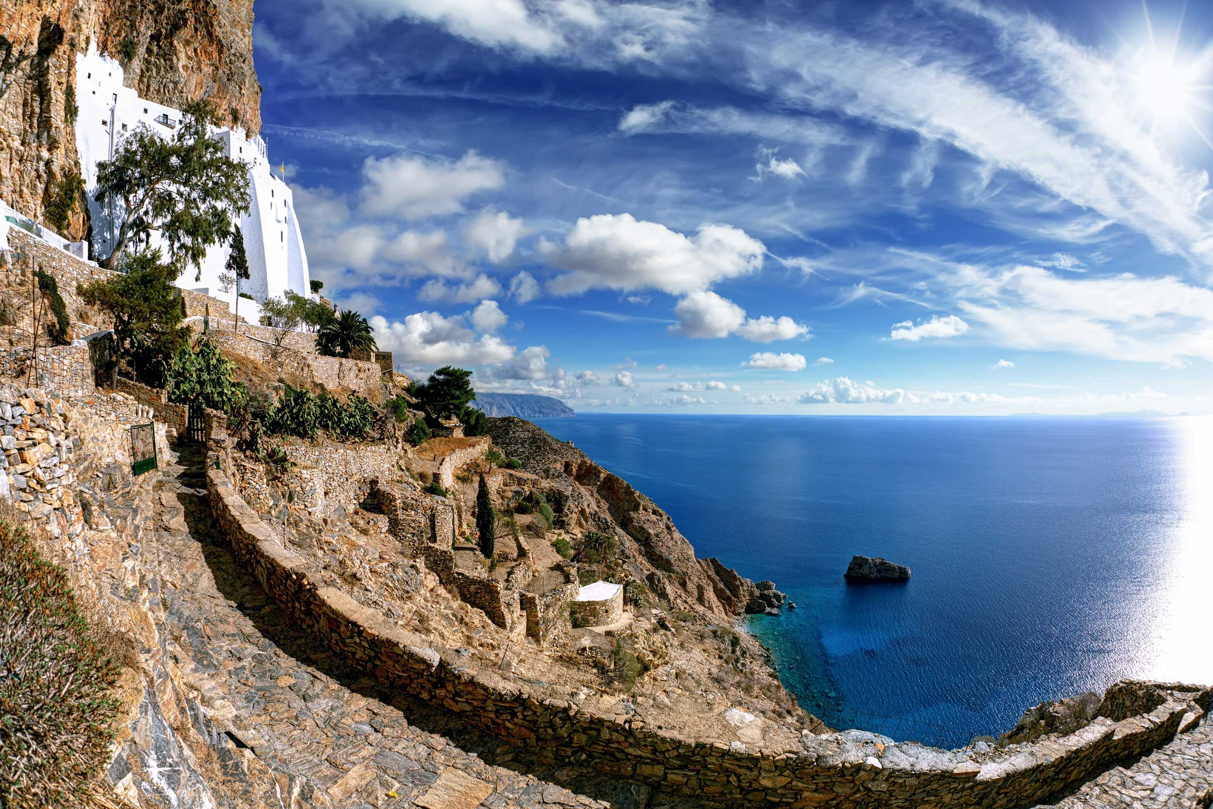 Pathway leading to a white monastery on a rocky cliffside overlooking a very blue sea and arcing clouds overhead, Greece