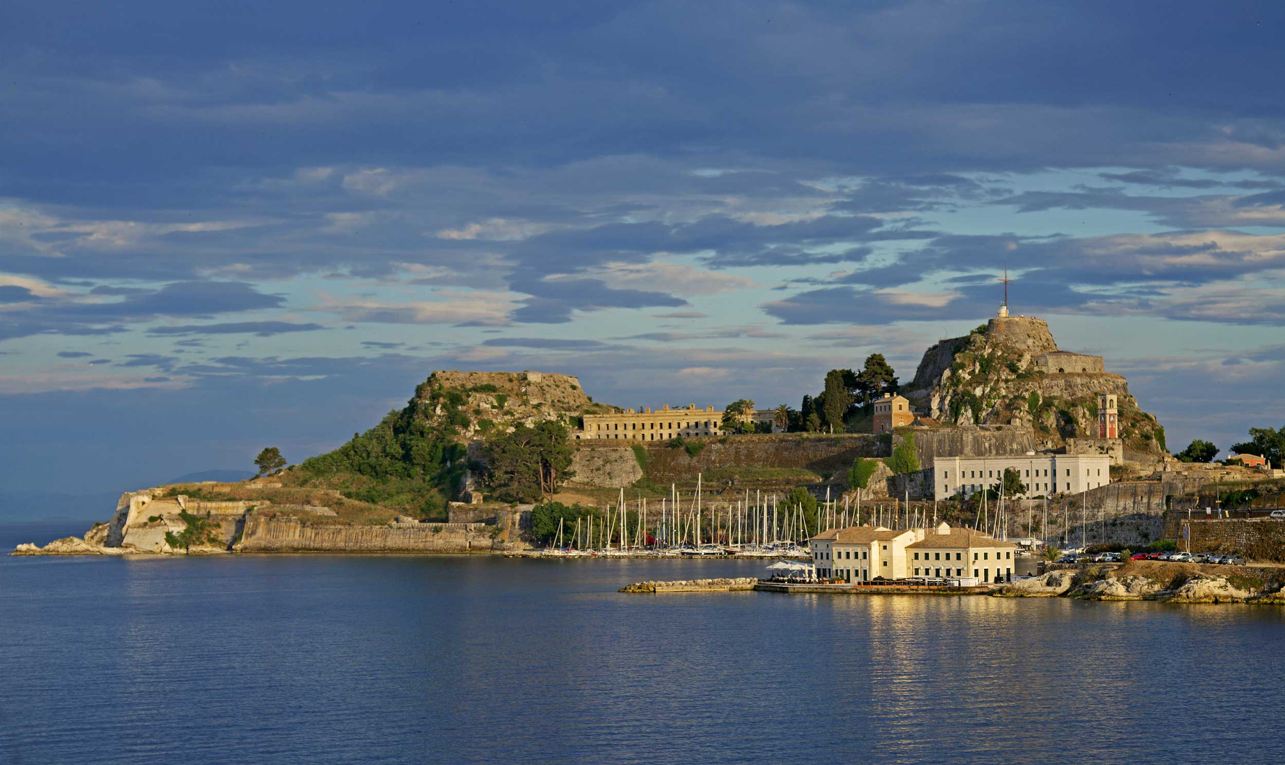 View across water towards a medieval town and fortresses on either side, Greece