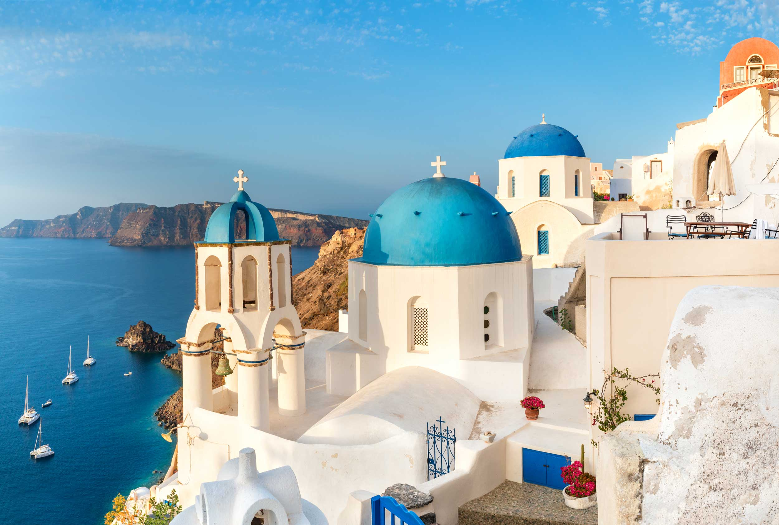 Three blue domes and white cuboid houses above a blue sea with boats below and islands in the distance, Greece