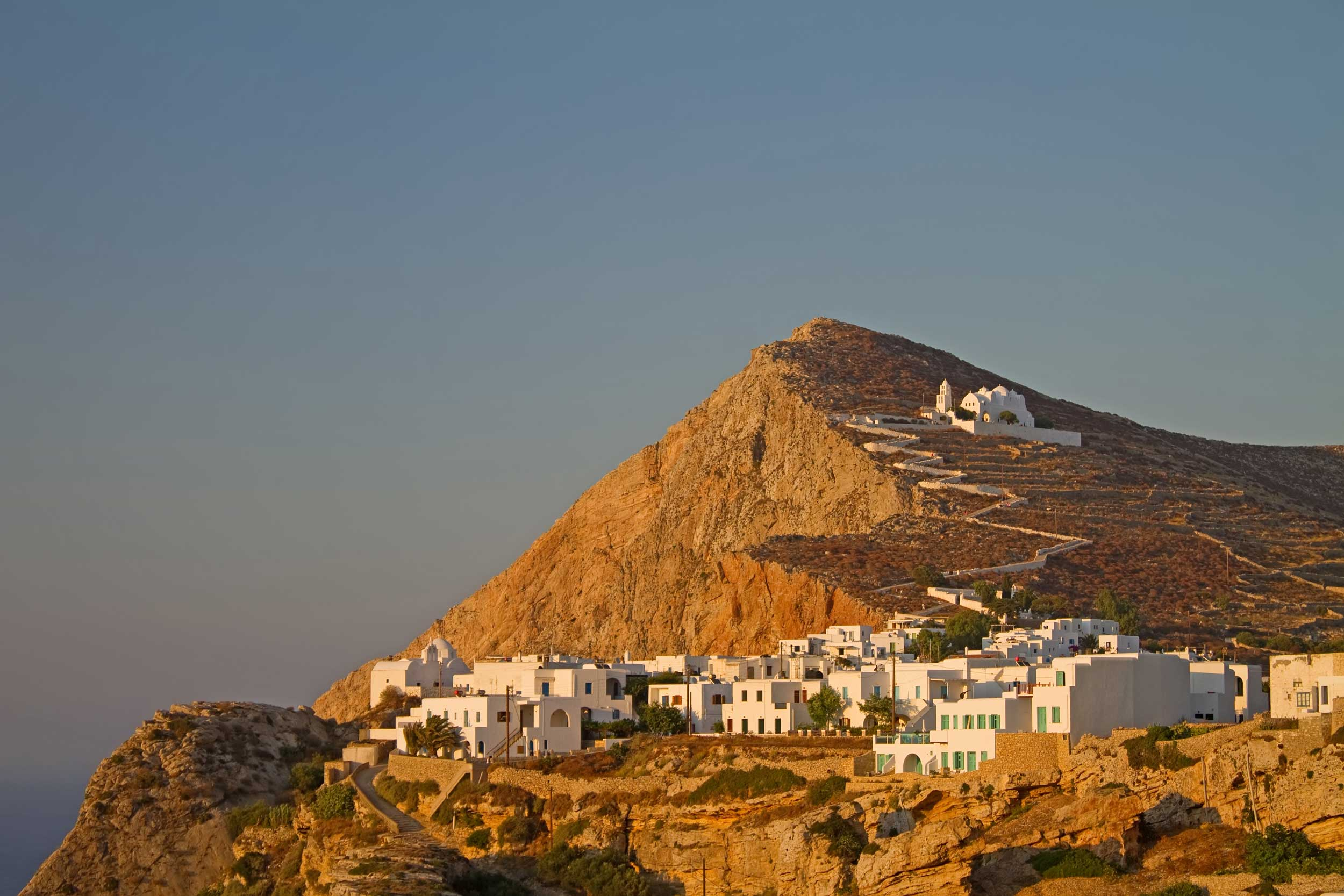 A village and a zigzag pathway up a rock hillside to a white church bathed in an orange glow, Greece