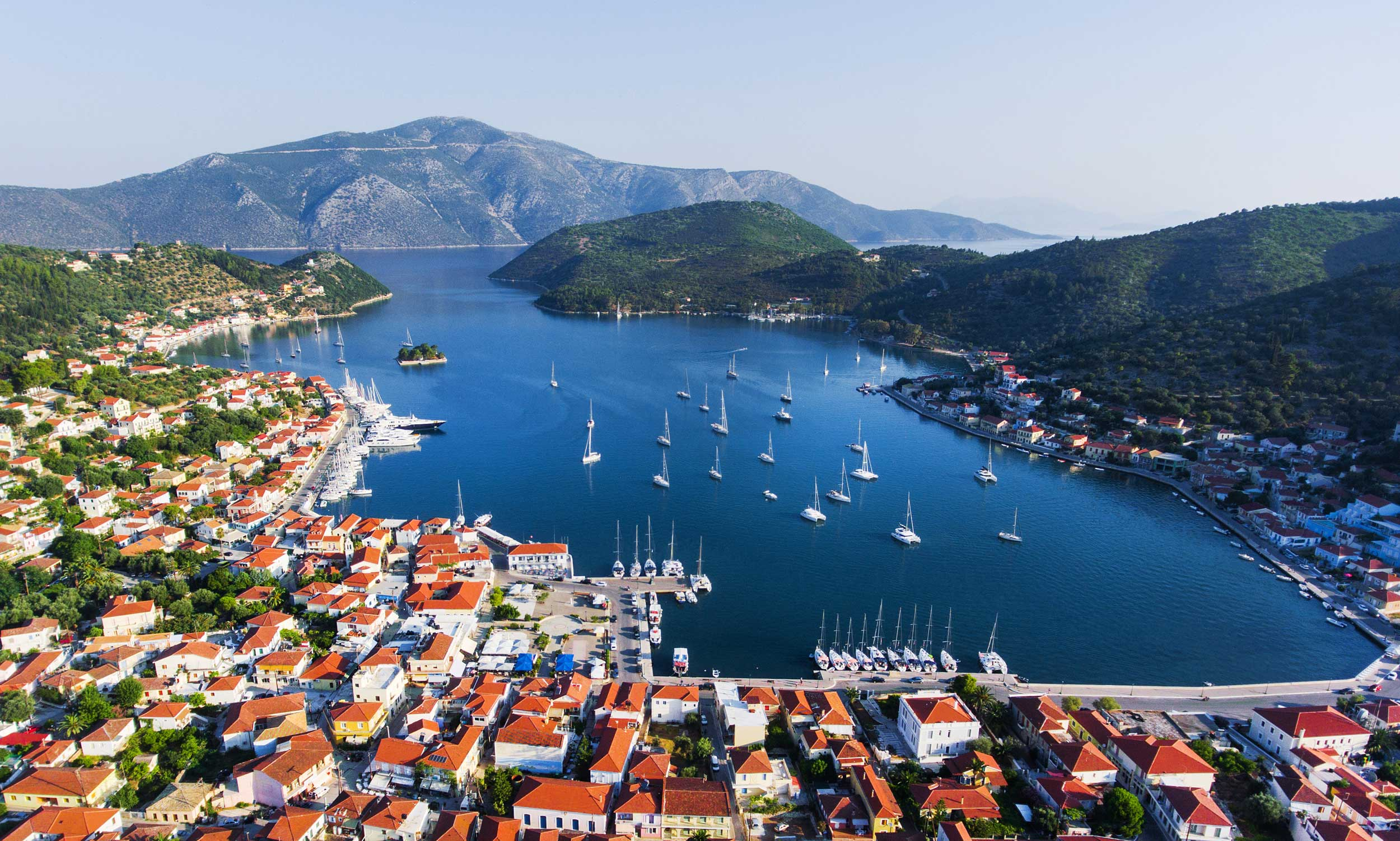 A large long, flat, calm harbour with moored boats, orange-roofed houses and sail boats sailing in enclosed by two hillsides, Greece