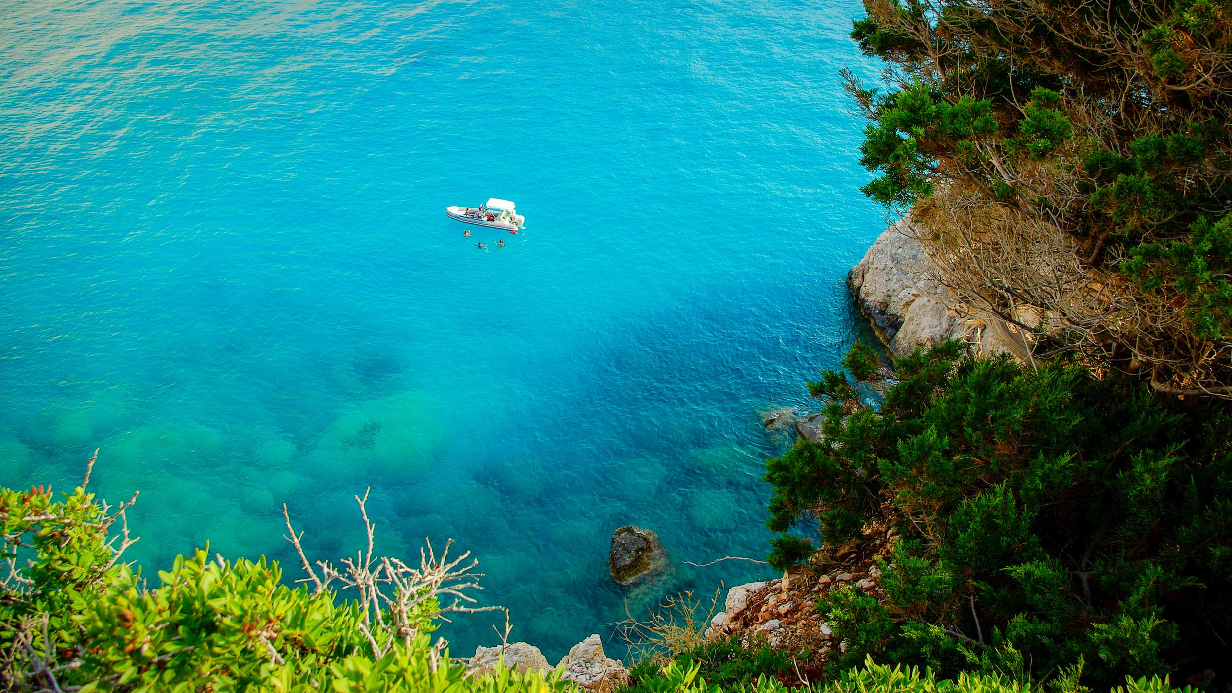 Looking down the side of a cliff onto a boat on crystal-clear blue sea with three swimmers by it, Greece