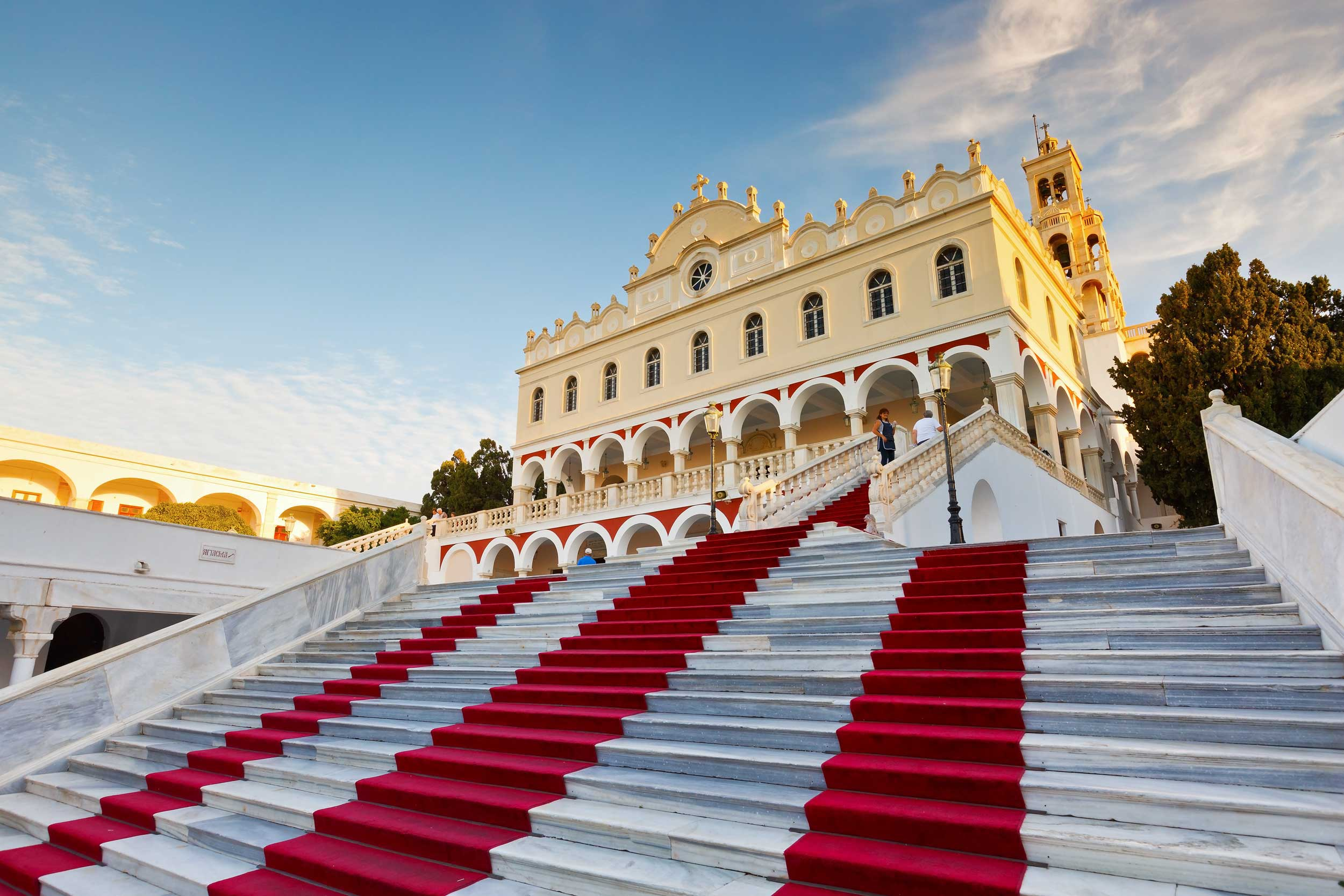 An imposing colonnaded building at the top of wide marble stairs lined with red carpets, Greece