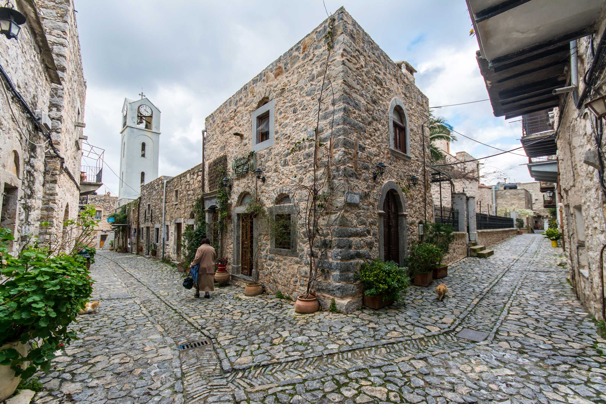 A cobblestoned medieval street corner with a white clocktower in the distance, Greece