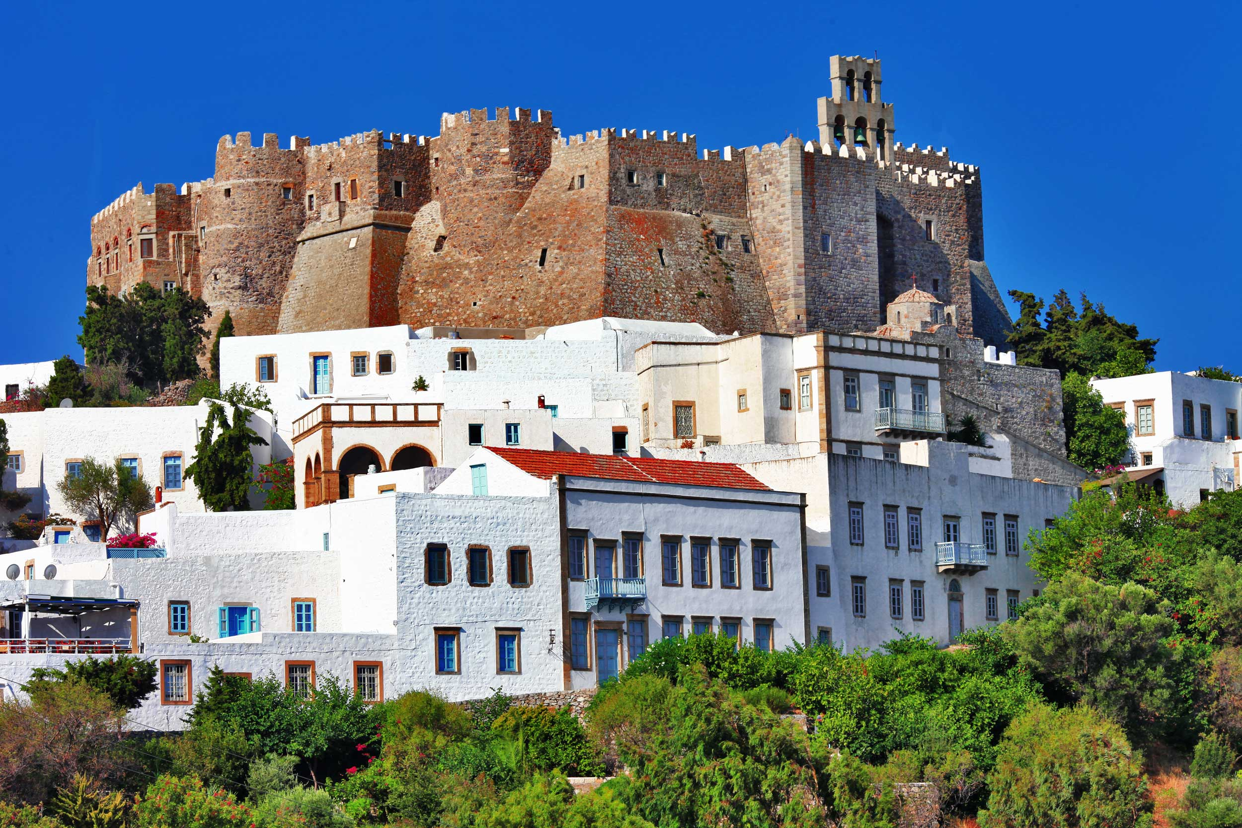 A fortress looming over whitewashed buildings on a hillside, Greece