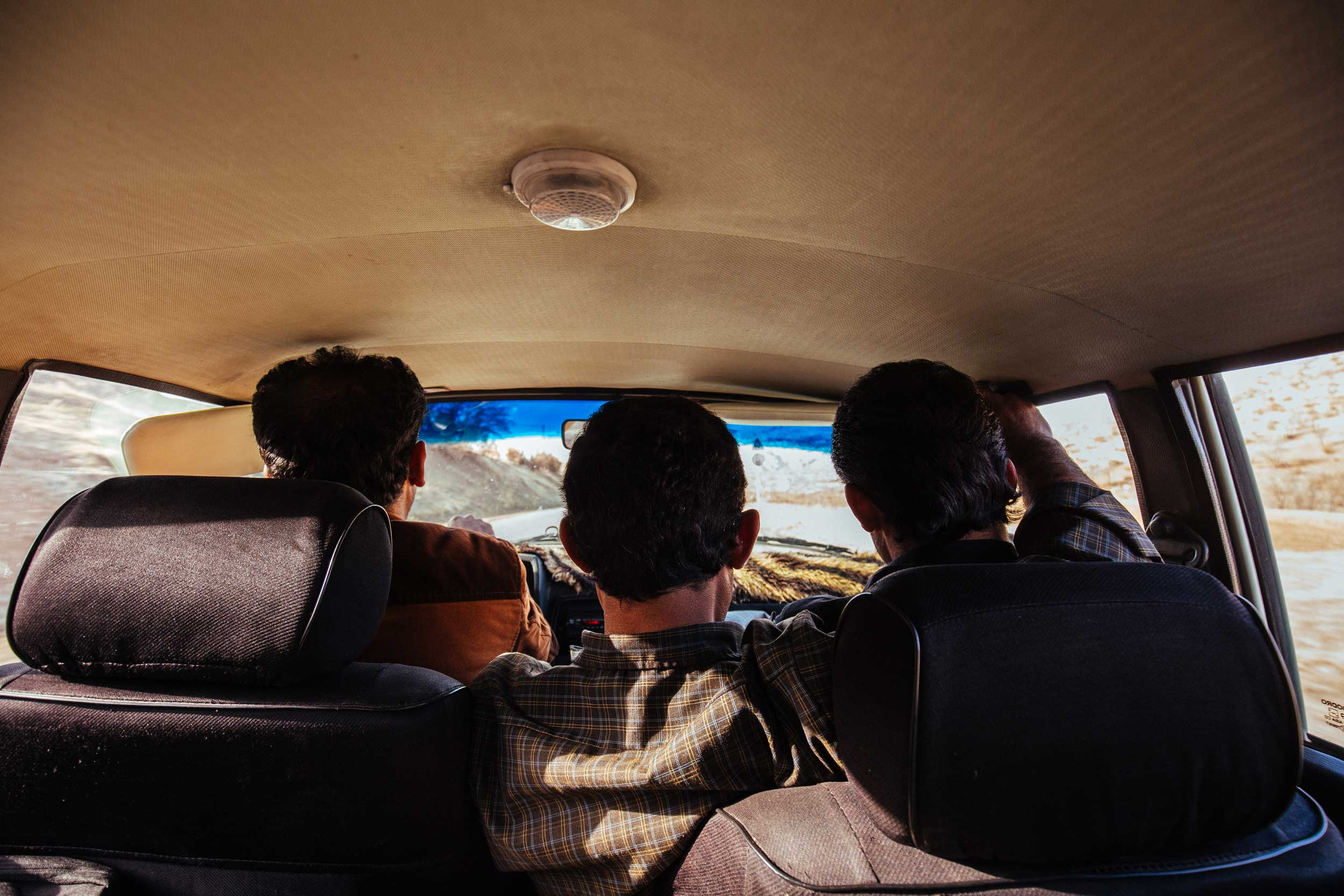 Rear shot of three men in a car facing out the windscreen in Iran