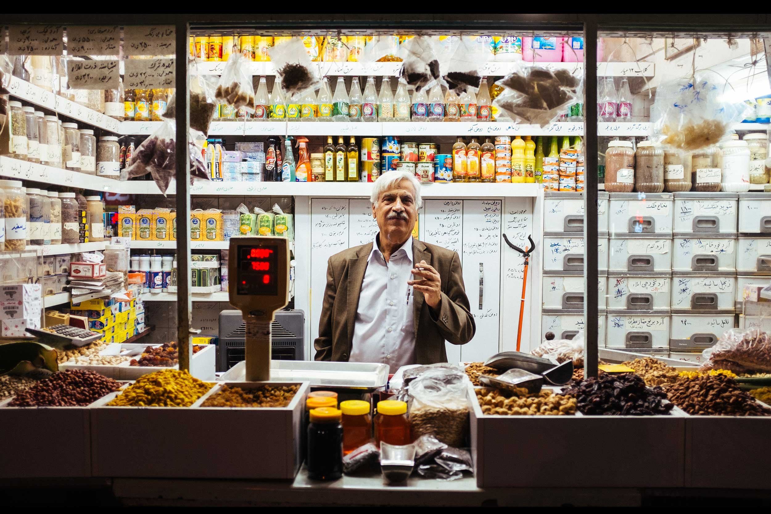 An Iranian man standingin his store with dried fruits and nuts piled up for sale, Palangan , Iran