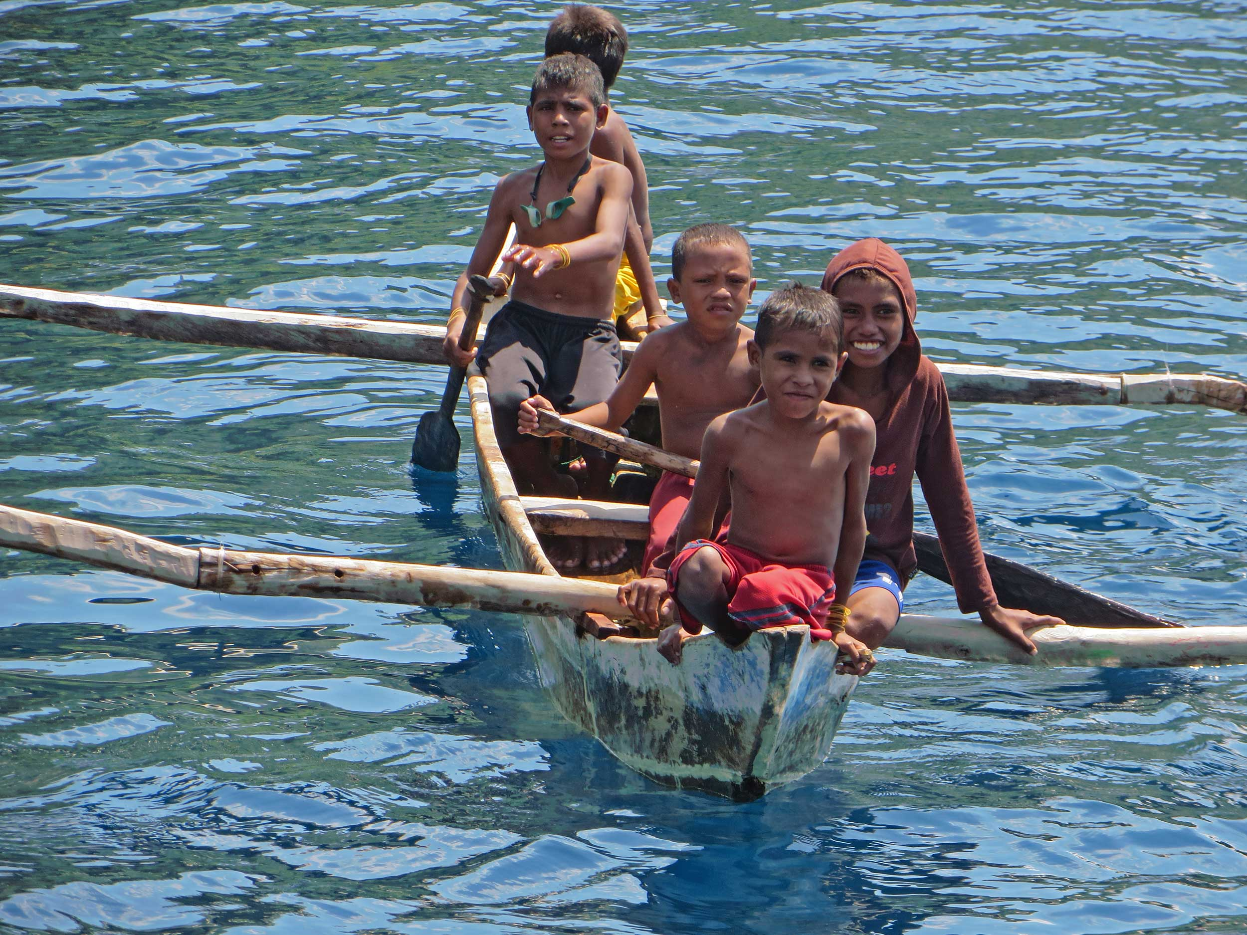 Five smiling village boys sailing on the water in an outrigger canoe
