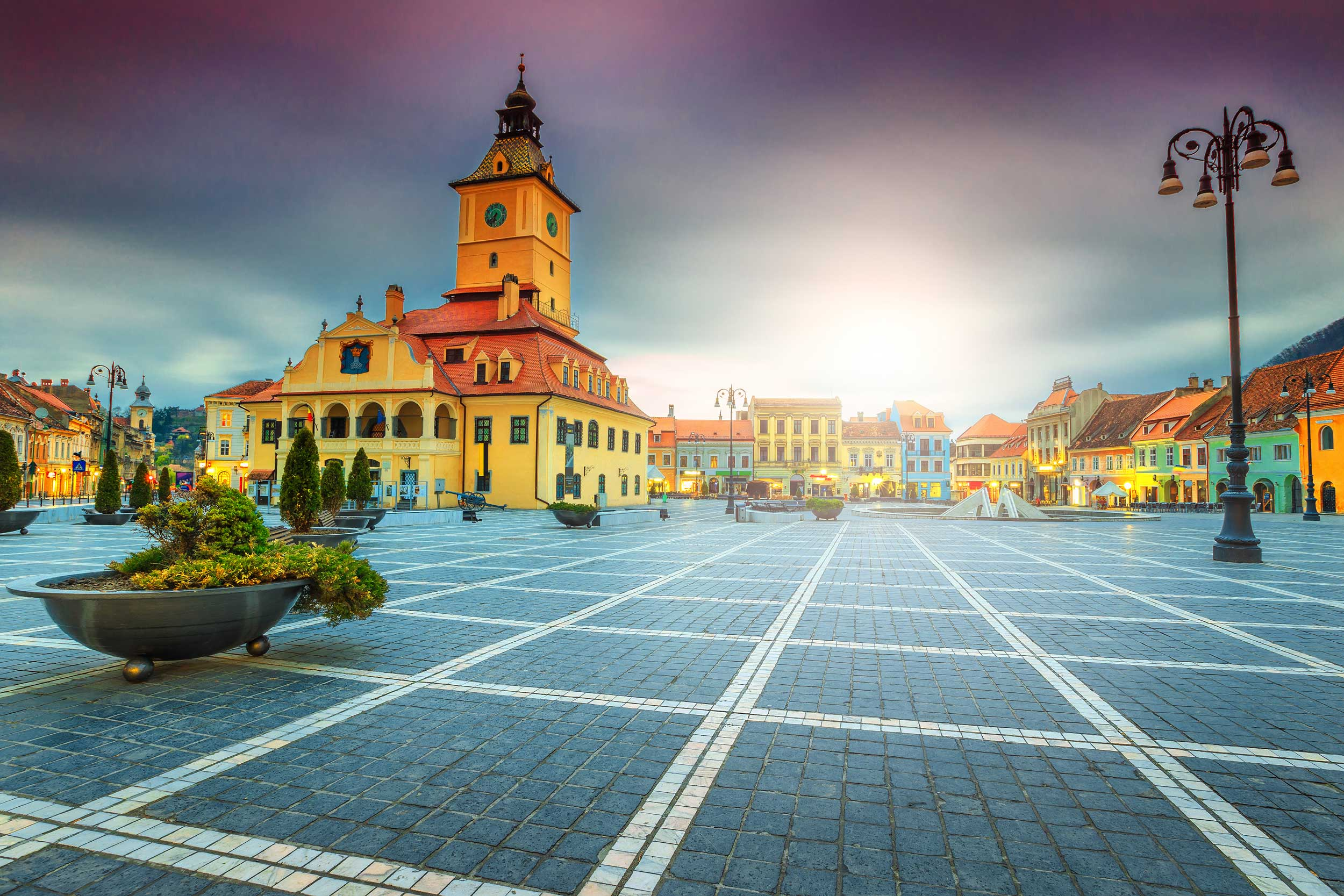 Long view down a cobbled town square with a steepled main building and assorted multi-coloured baroque buildings ringing the square, Brasov