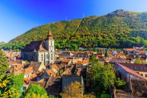 View of a red-tile roofed medieval town nestled at the bottom of a forested hill with letters BRASOV placed at the peak