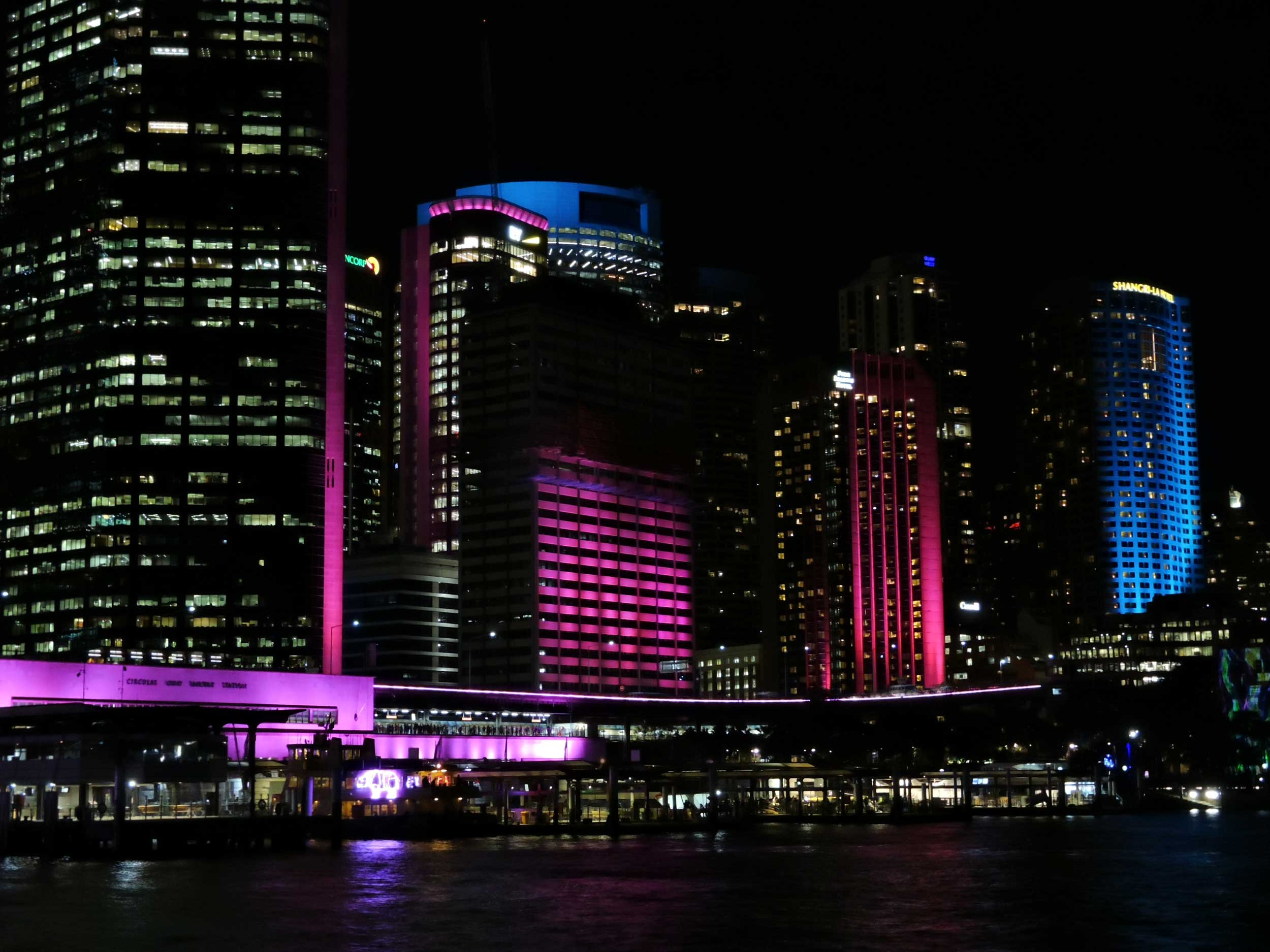 Lighted-up , multi-coloured skyscrapers bt the river, Vivid, Sydney