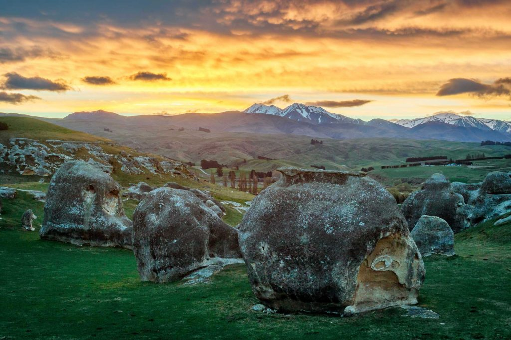 The Elephant Rocks seem to be placed by giants, decorating the green pastures of local farmers. Here, the sky turns to fire to light them, Duntroon, northern Otago.