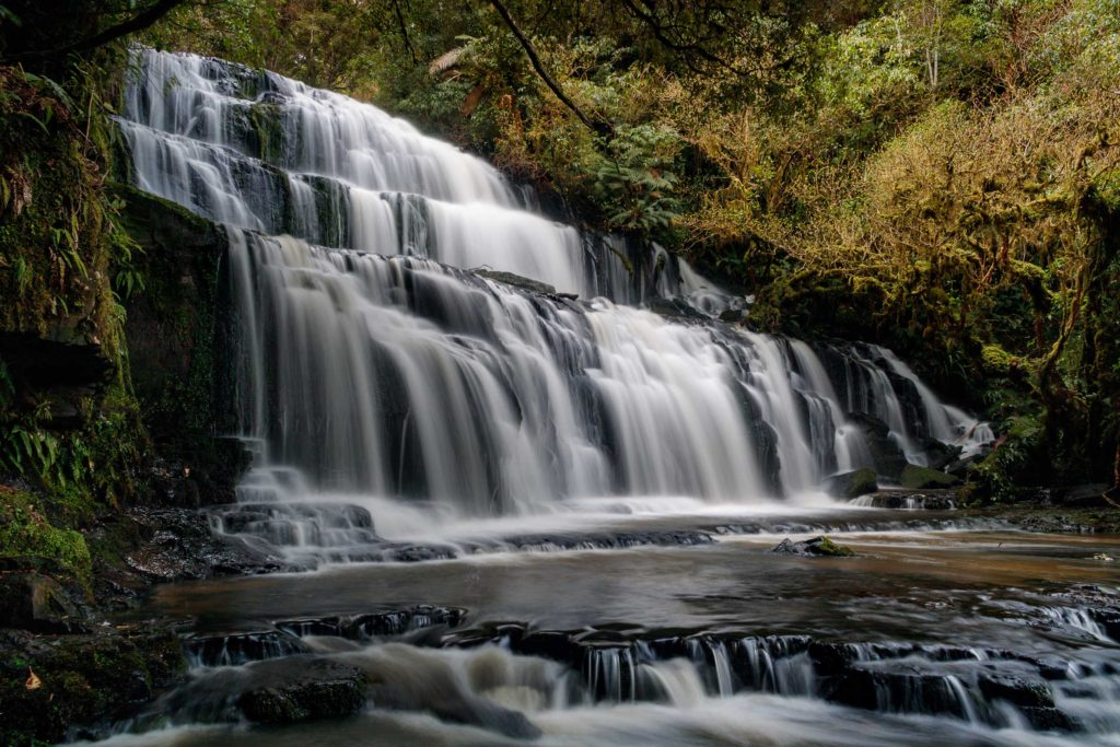 Purakaunui Falls is hidden within the Catlins, down a short track into the jungle. The roaring water pours over wide stone steps, creating the perfect atmosphere to lose one's self in a dream, Owaka, southern Otago.