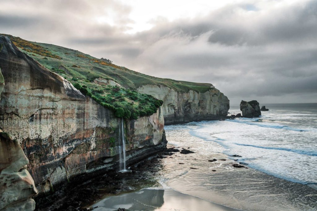 On a cloudy day, a waterfall pours over the edge of a cliff, splattering in the sand below, Tunnel Beach, Dunedin, eastern Otago.