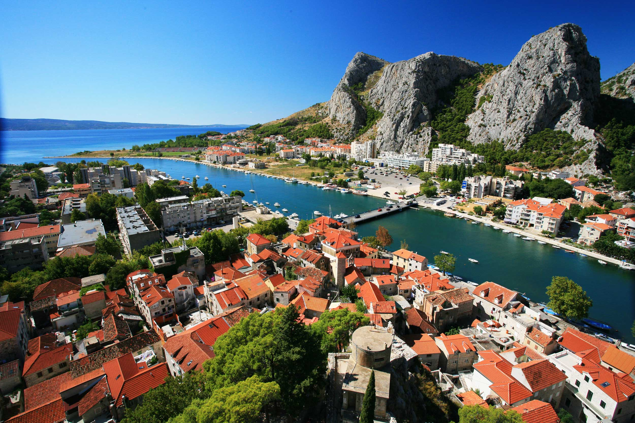 Red-roofed town on either side of a river with a bridge between them and rocky crags in the background, Omis, Croatia