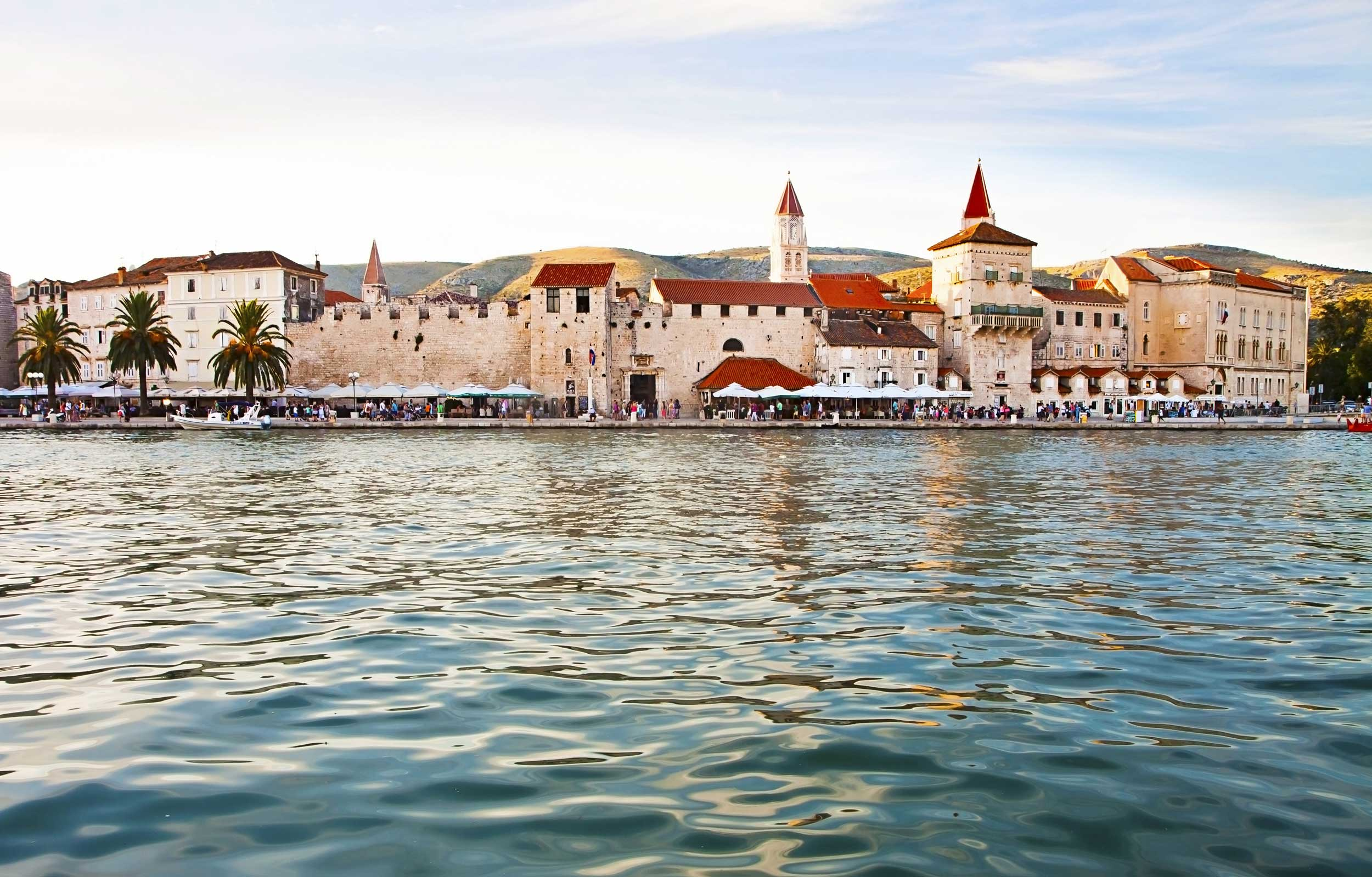 View across water to a white-walled red-roofed medieval structures by a promenade, Croatia