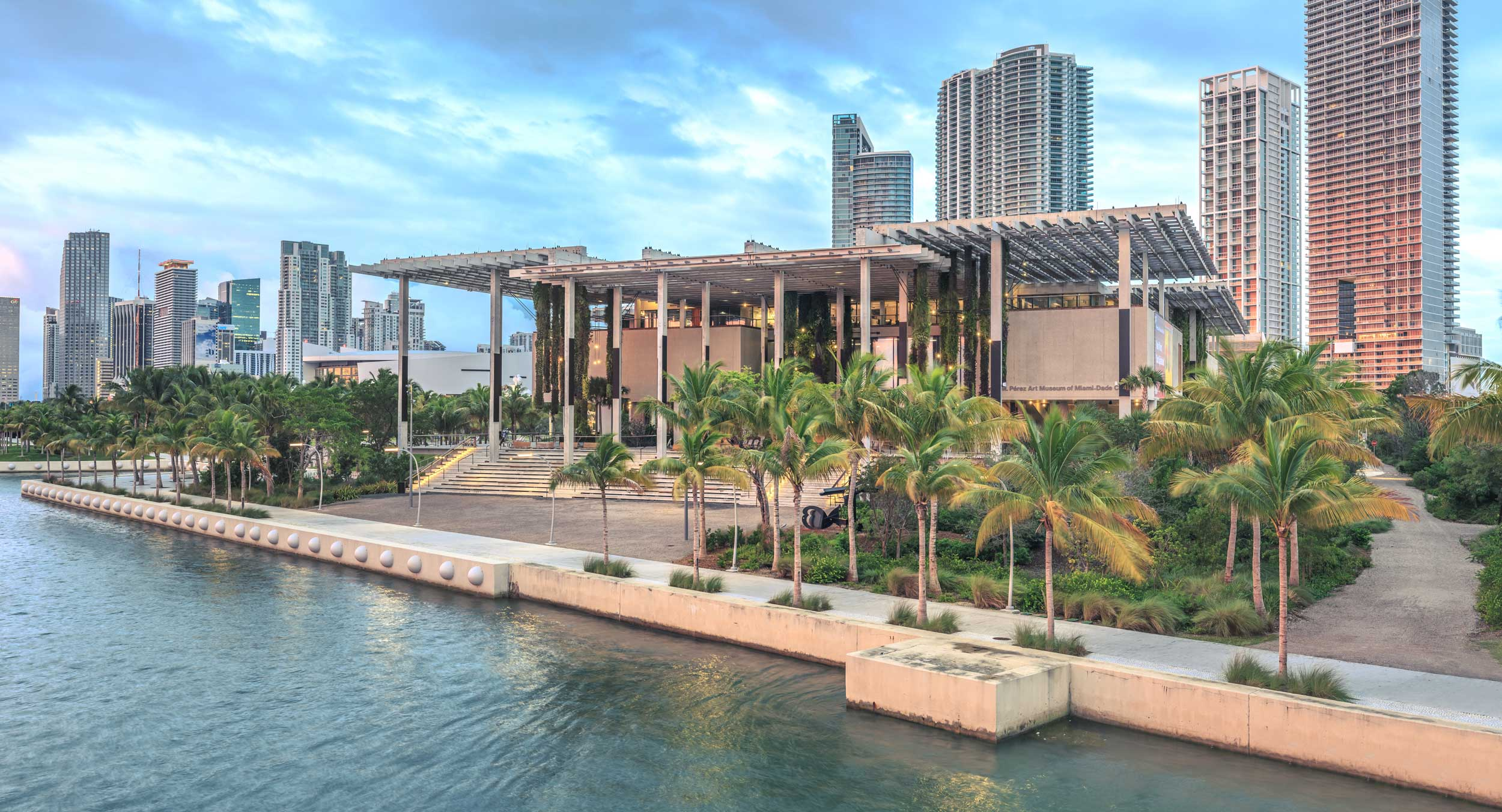 Building with thin-pillared portico by tha water with palm trees lining the water, Miami