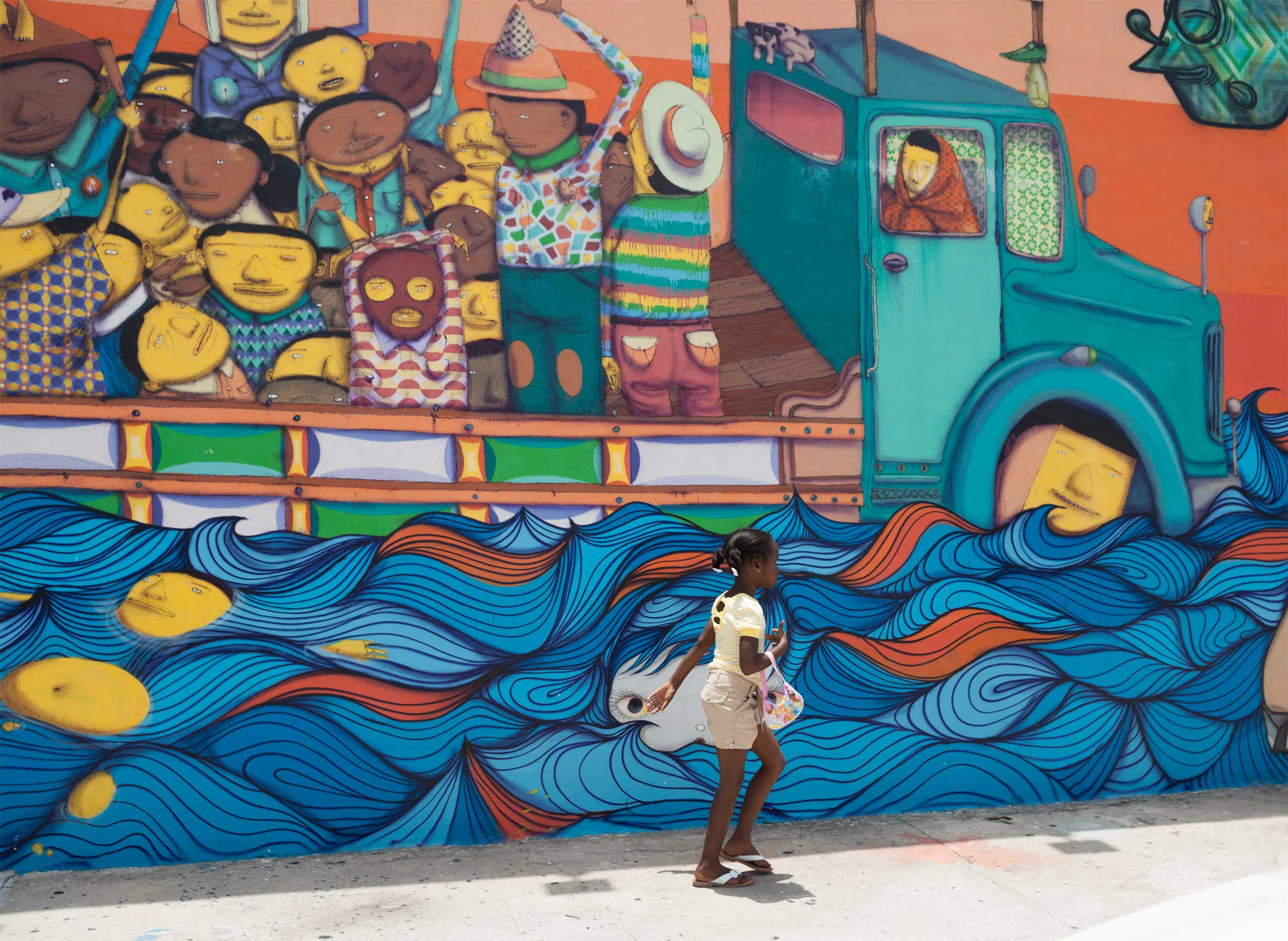 Child with a little handbag walking past a mural of a flat-bed truck carrying multiple people fording water