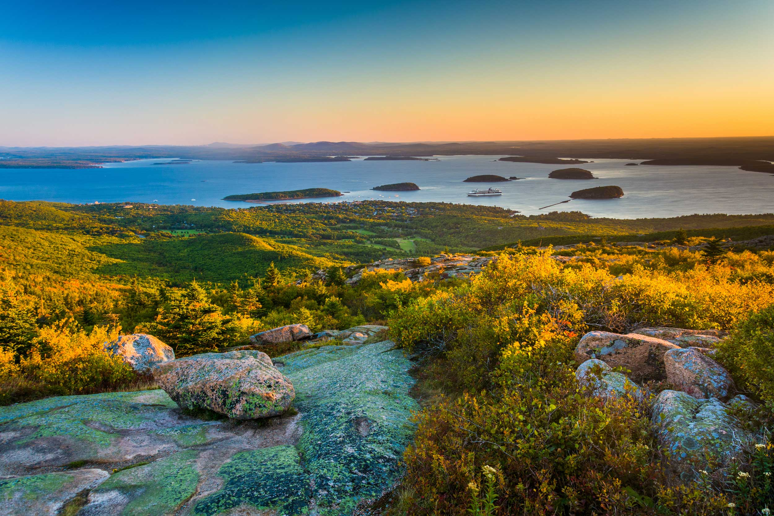 View over a mountaintop towards a town, several small islands in the sea and an orange glow in the sky, Bar Harbor
