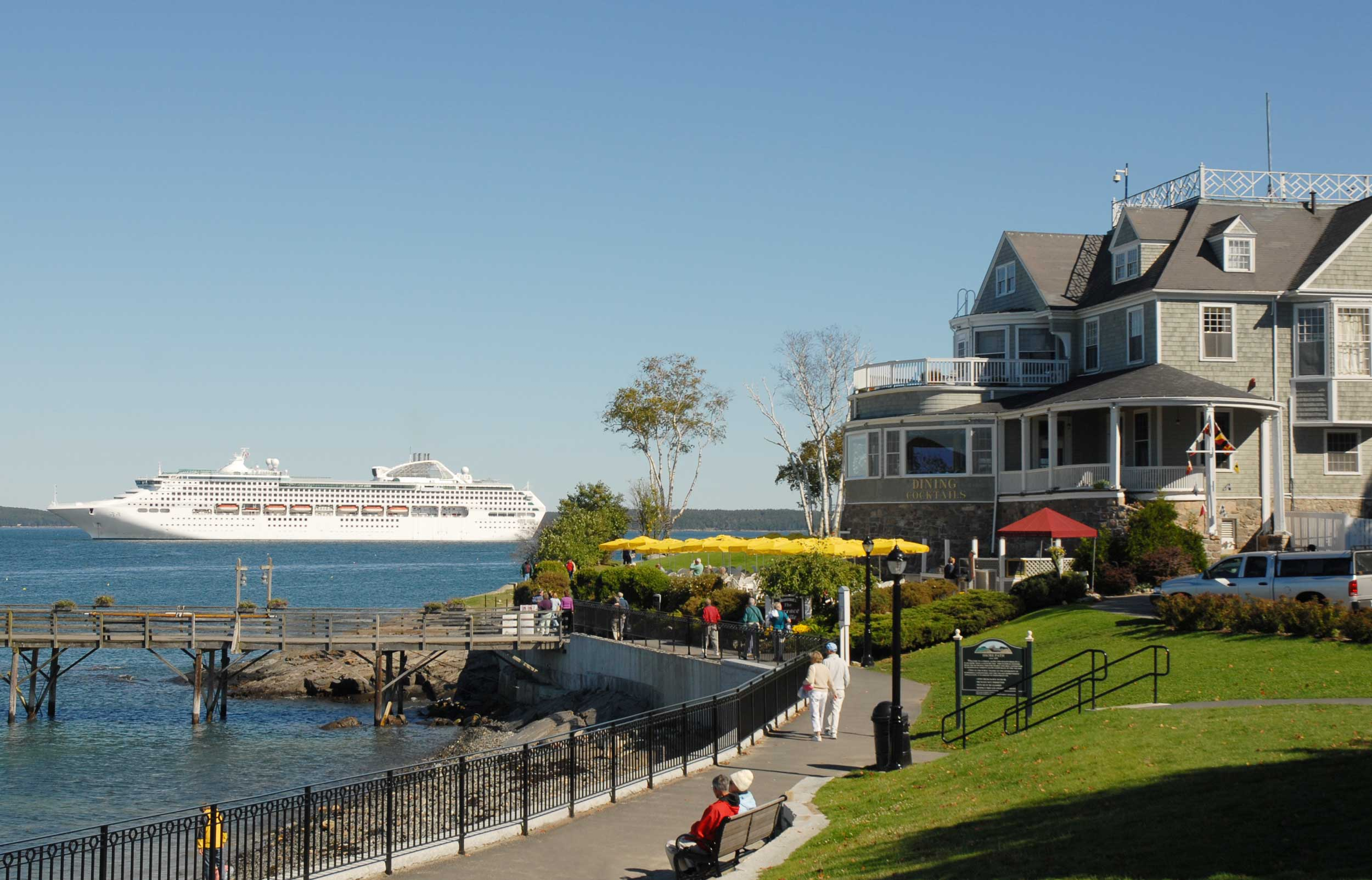 People walking and seated along a path by the shore, with a historical building and cruise ship in the background, Bar Harbor