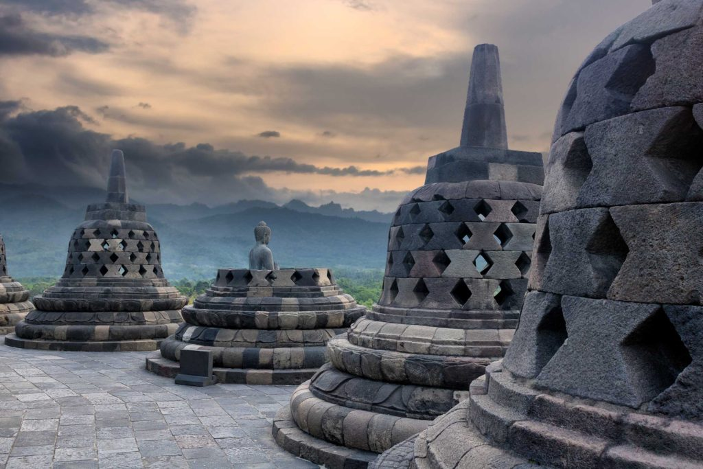 Borobudur is a temple and UNESCO World Heritage site in central Java, Indonesia. The iconic bells each contain a sitting Buddha. The setting sun lights up the sky as the Buddha looks outward.