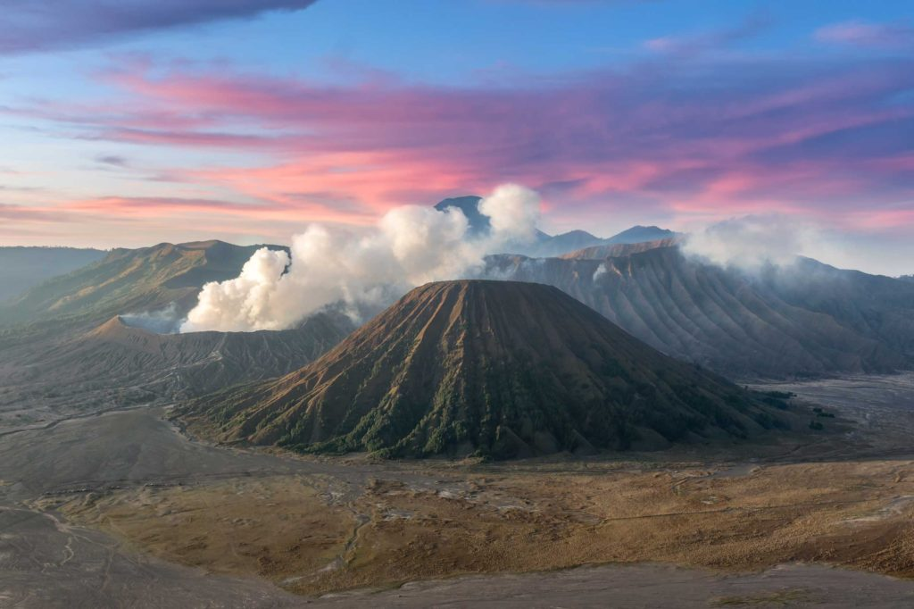 Mt Bromo is an active volcano on the island of Java. In 2015 its activity level started to rise, stirring fear and curiosity as to when it may erupt again. Here you can see the smoke rising from the crater at sunrise.