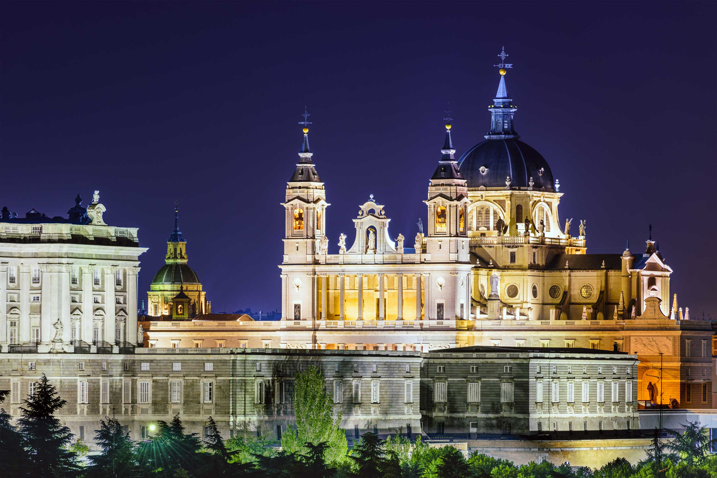 A lit-up blue-domed cathedral with in Madrid