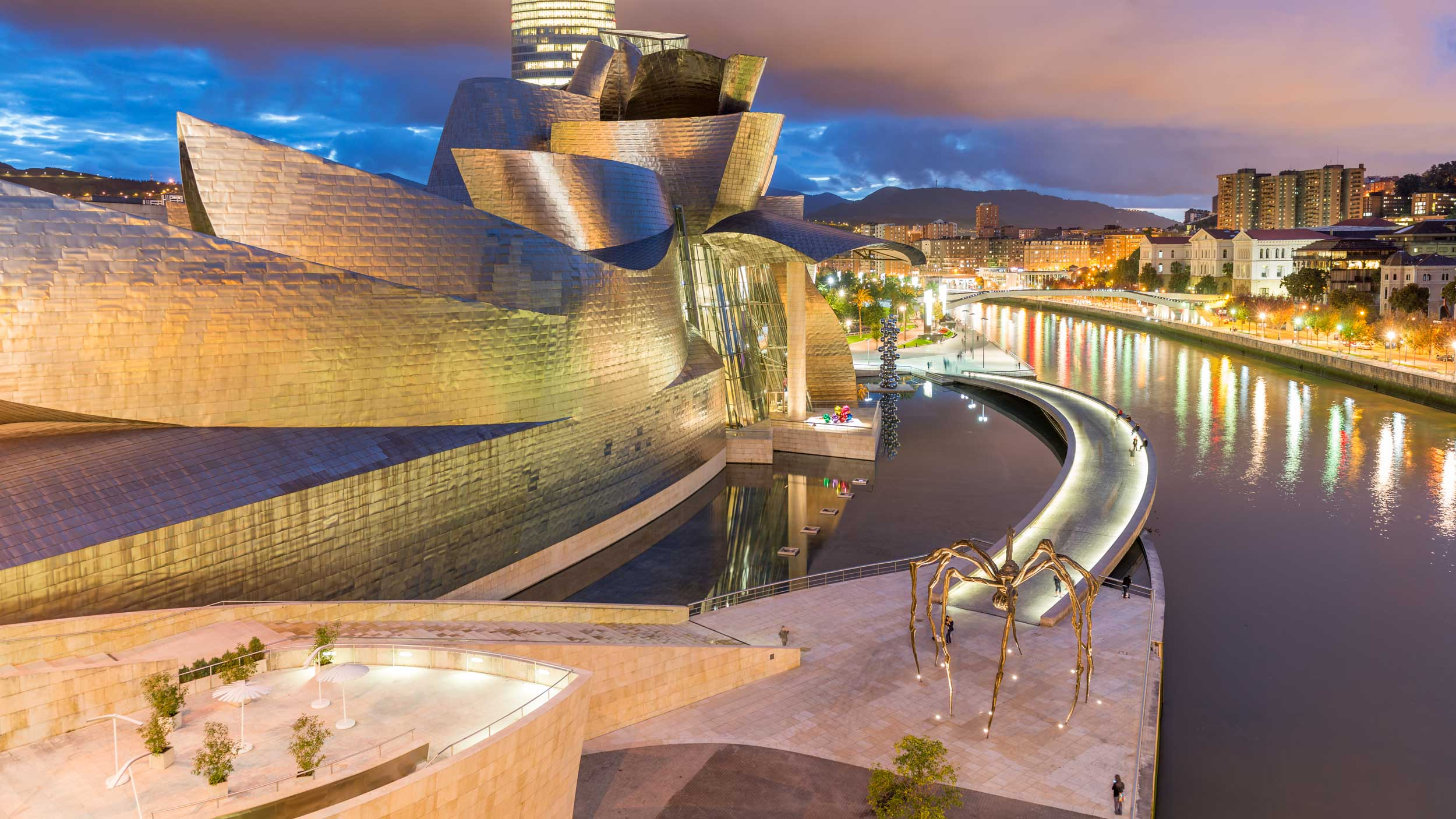 An undulating building on the banks of a river, Bilbao, Spain