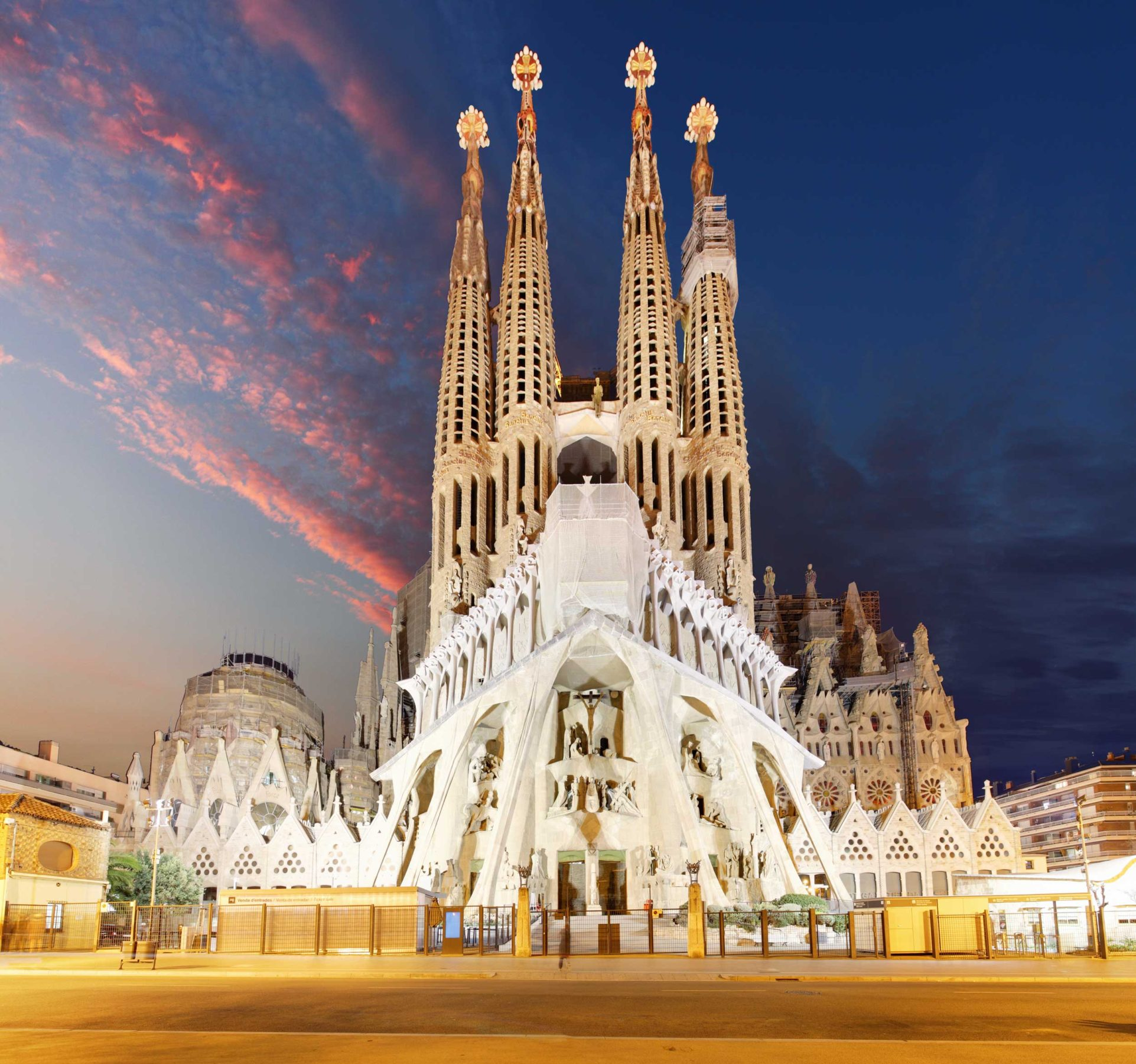 A brightly-lit, elaborately-designed, multi-spired cathedaral in Barcelona, Spain