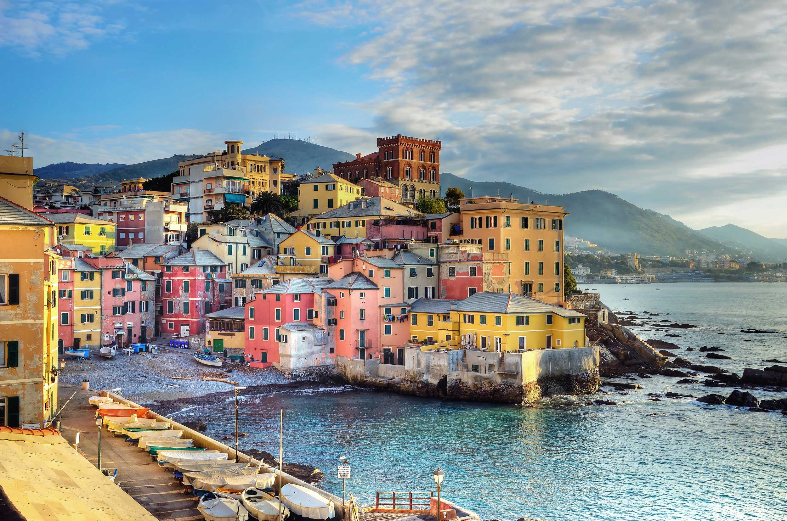 Pastel coloured buildings by the sea with landed fishing boats on the side, Genoa.