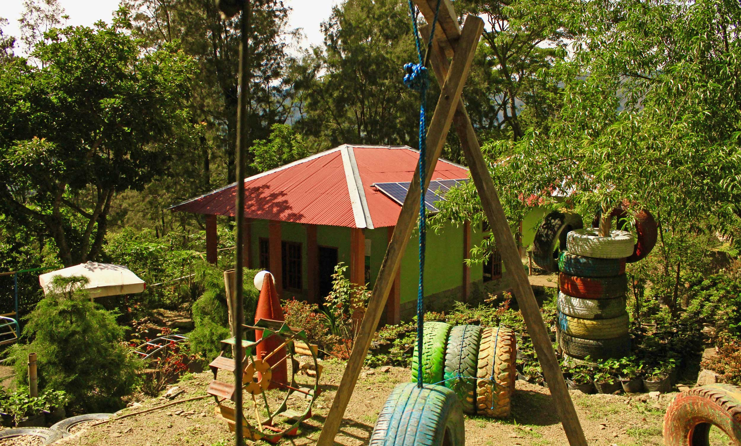 A playground with tyres for equipment and a green building with solar panels on its red roof, Timor-Leste