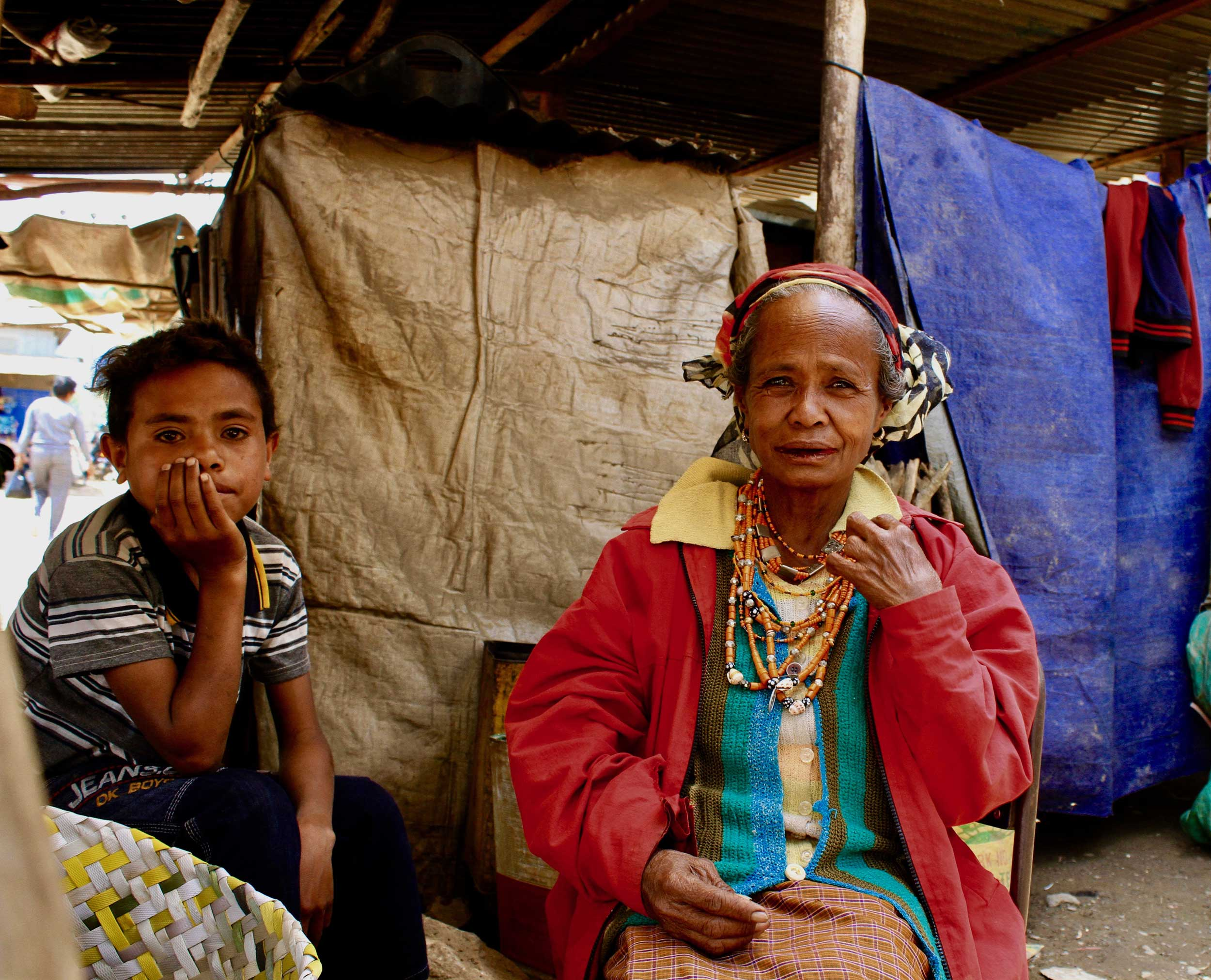 An elderly lady and a young boy at a market in Timor-Leste