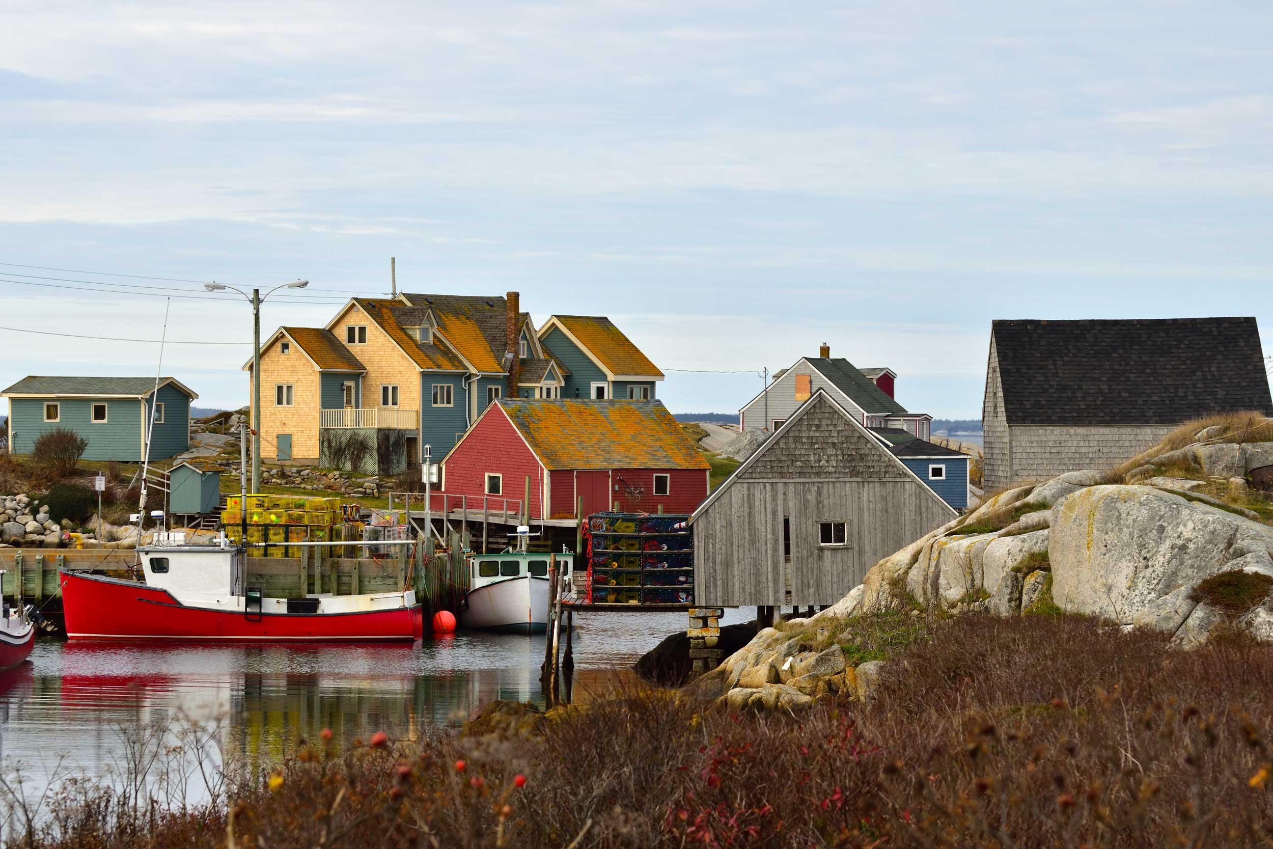 A red boat on water amongst brightly coloured buildings, Peggy's Cove, Halifax