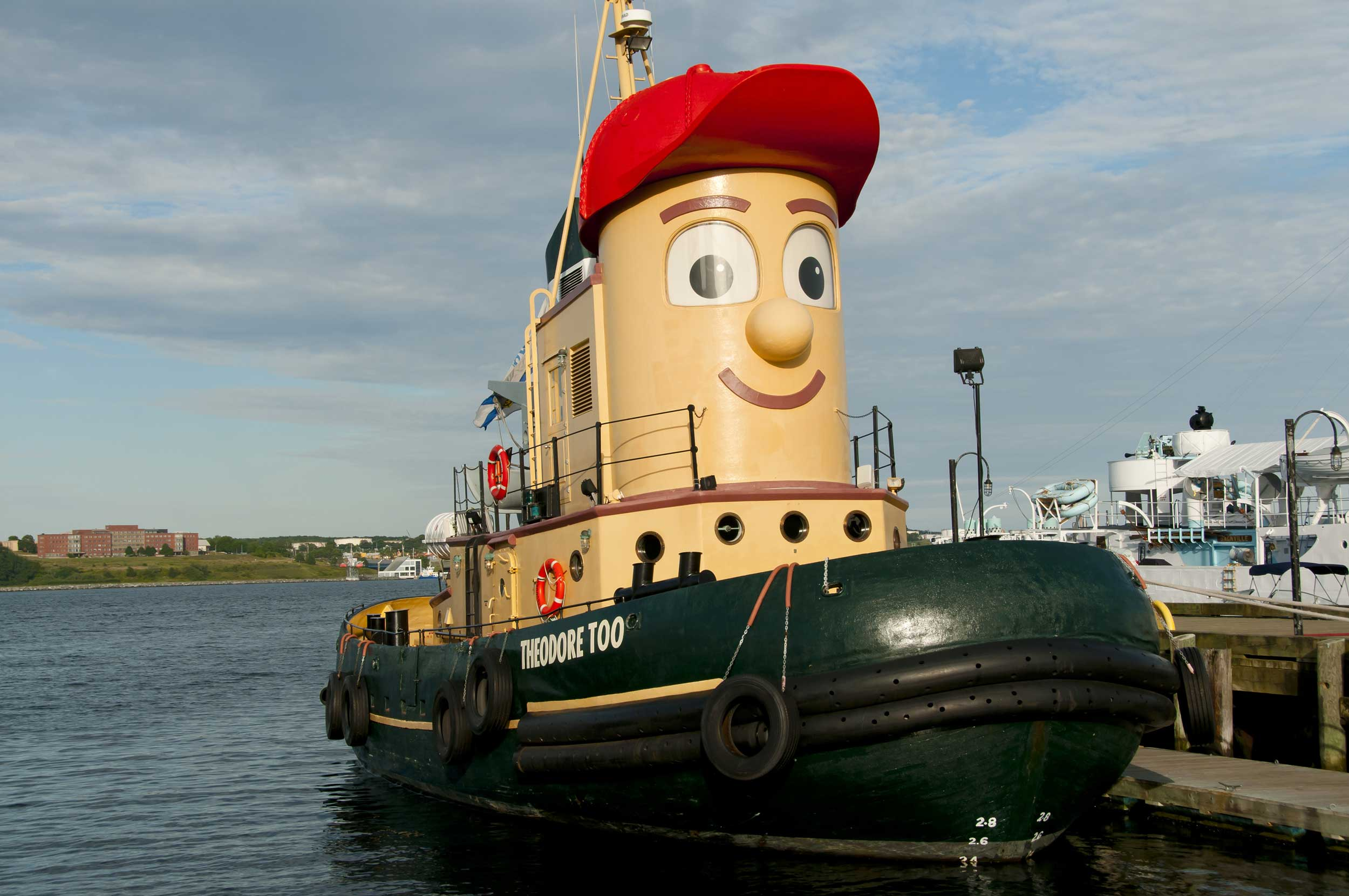 A tugboat done up as a cartoon figure by a pier, Halifax
