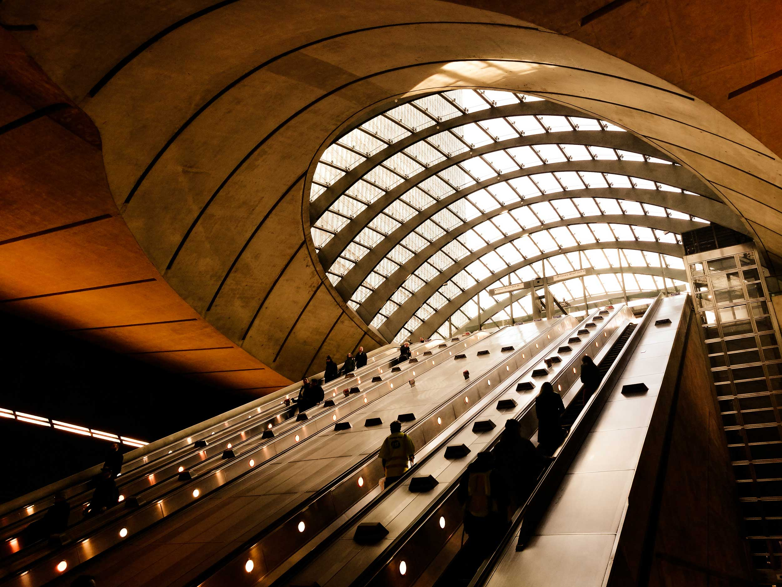 Escalators ascending towards a curved bank of glass in the ceiling, London
