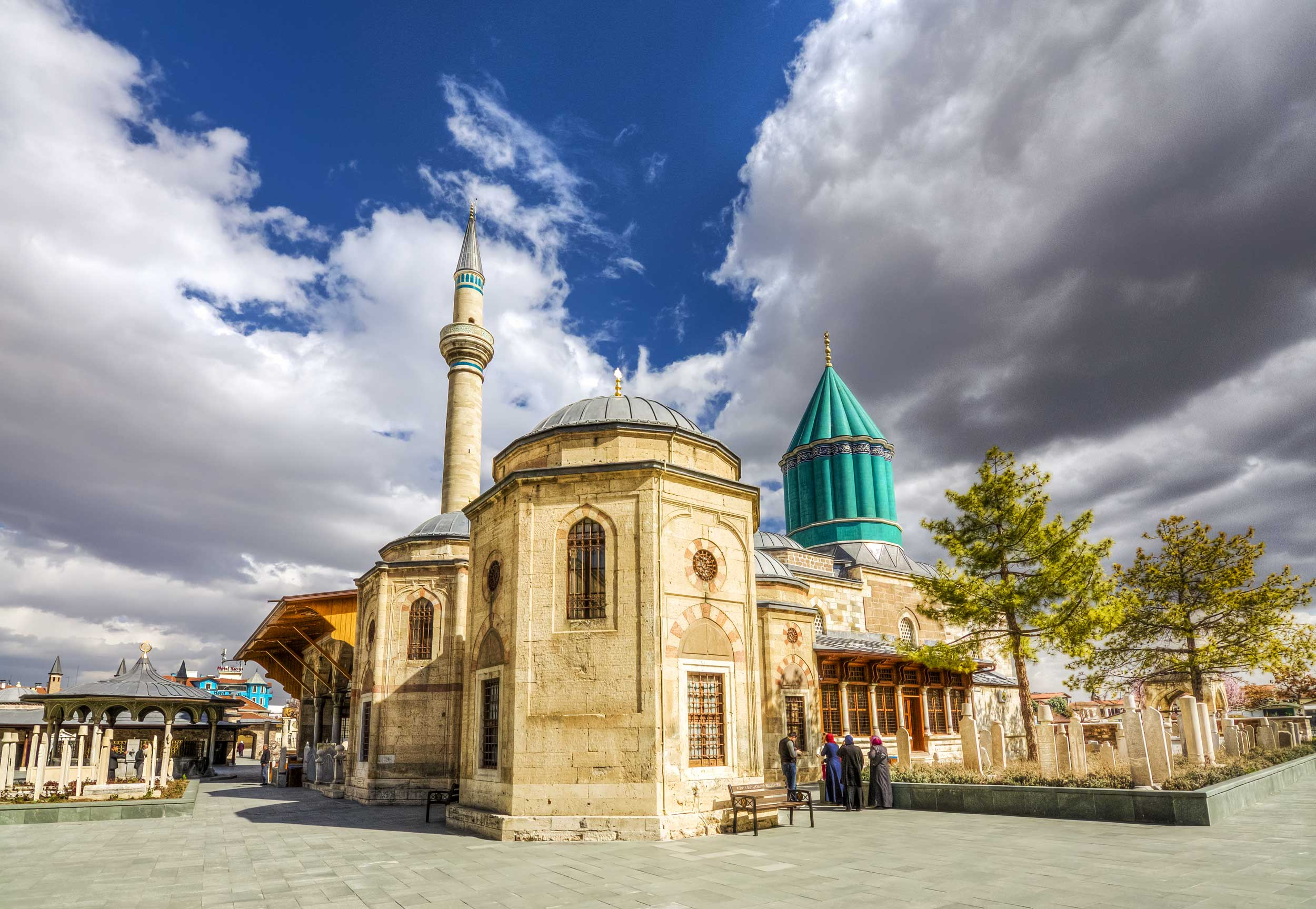 A large stone building with a green conical dome, Konya, Turkey