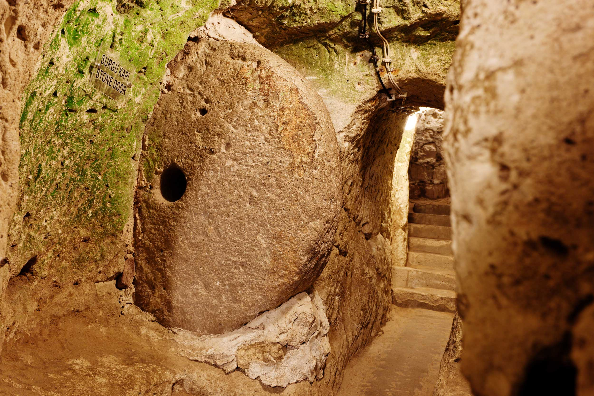 An underground passageway to some steps with a circular rock on the side, Turkey