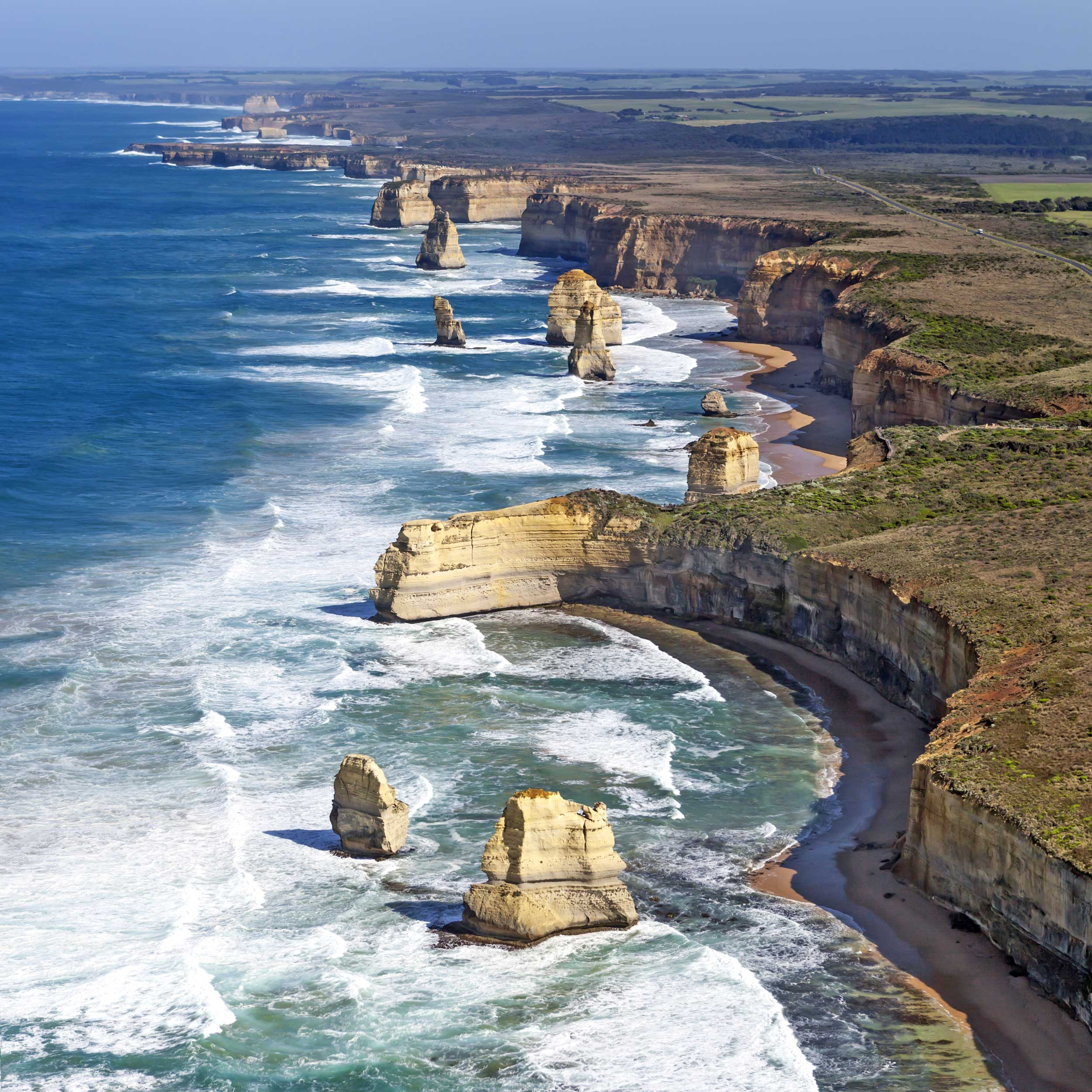 Cliffs extending down a coastline with limestone stacks in the foamy sea, Australia